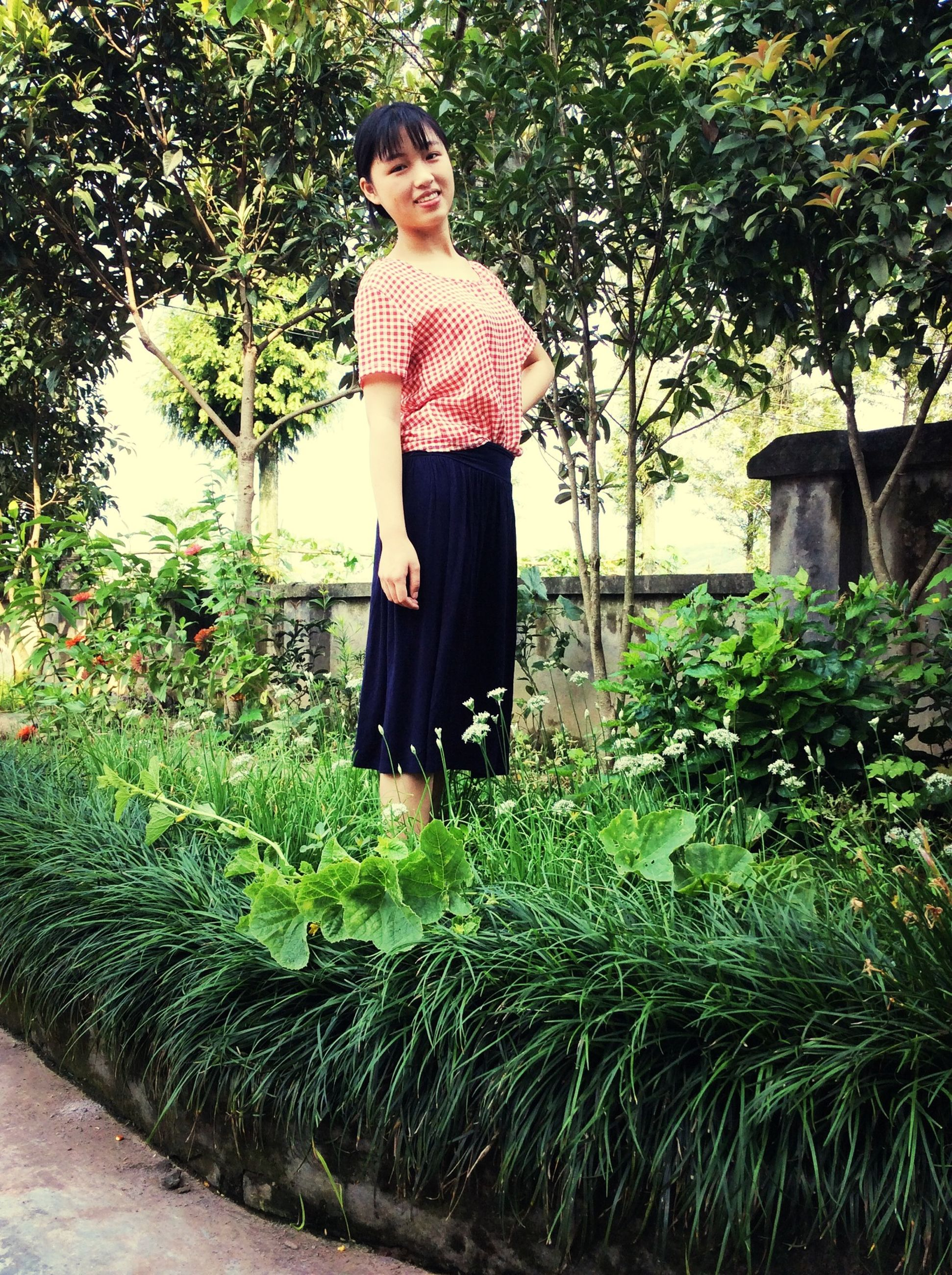 person, casual clothing, lifestyles, tree, young adult, full length, leisure activity, front view, standing, looking at camera, portrait, smiling, plant, young women, growth, three quarter length, happiness, green color