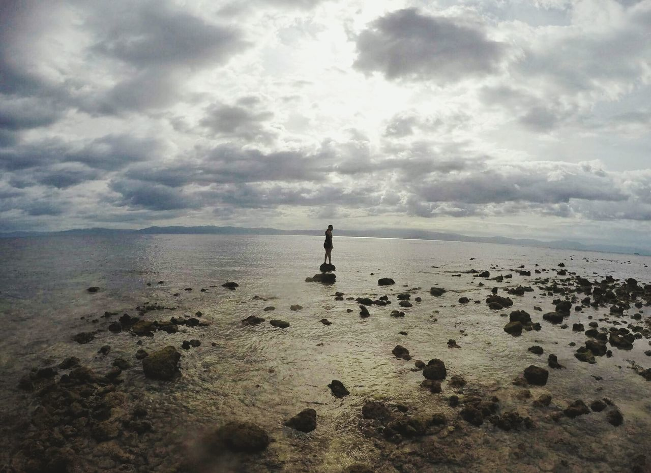 sea, horizon over water, sky, water, tranquil scene, beach, nature, tranquility, cloud - sky, scenics, outdoors, beauty in nature, rock - object, day, sand, one person, standing, full length, people