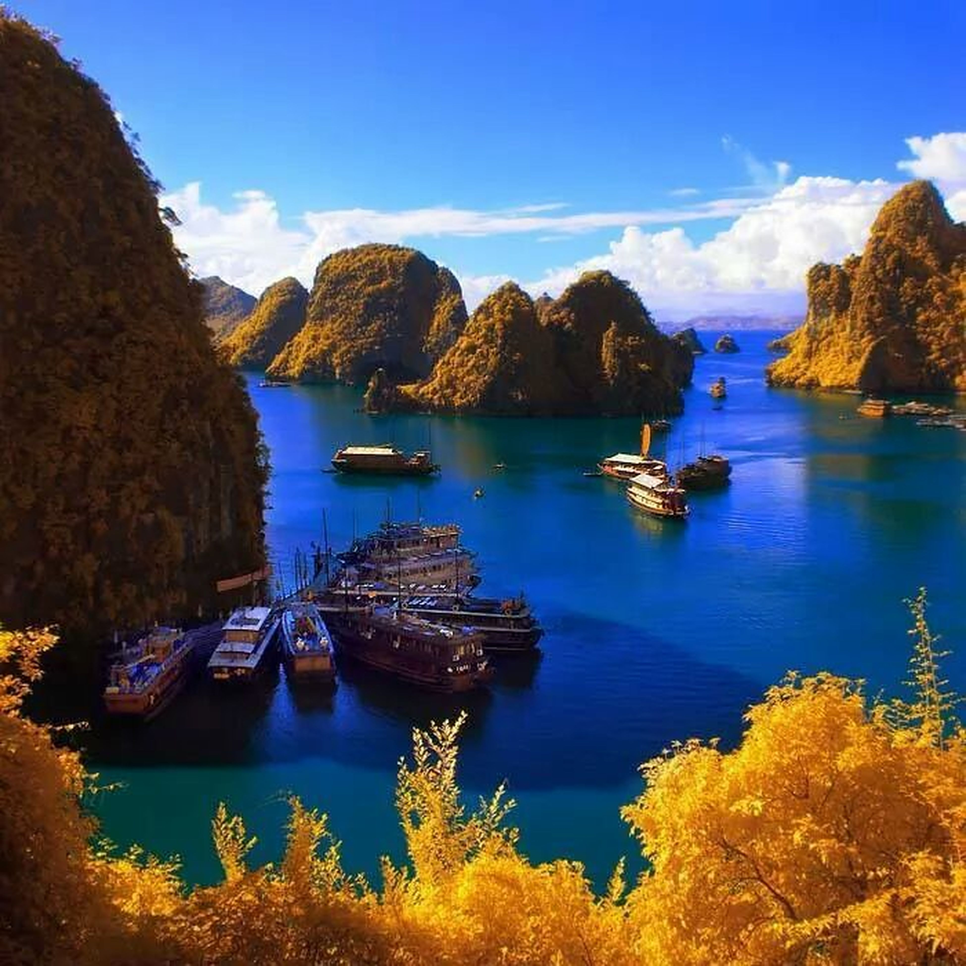 water, nautical vessel, transportation, boat, mode of transport, tranquil scene, tranquility, scenics, sea, sky, moored, blue, beauty in nature, mountain, rock formation, nature, rock - object, tree, idyllic, travel