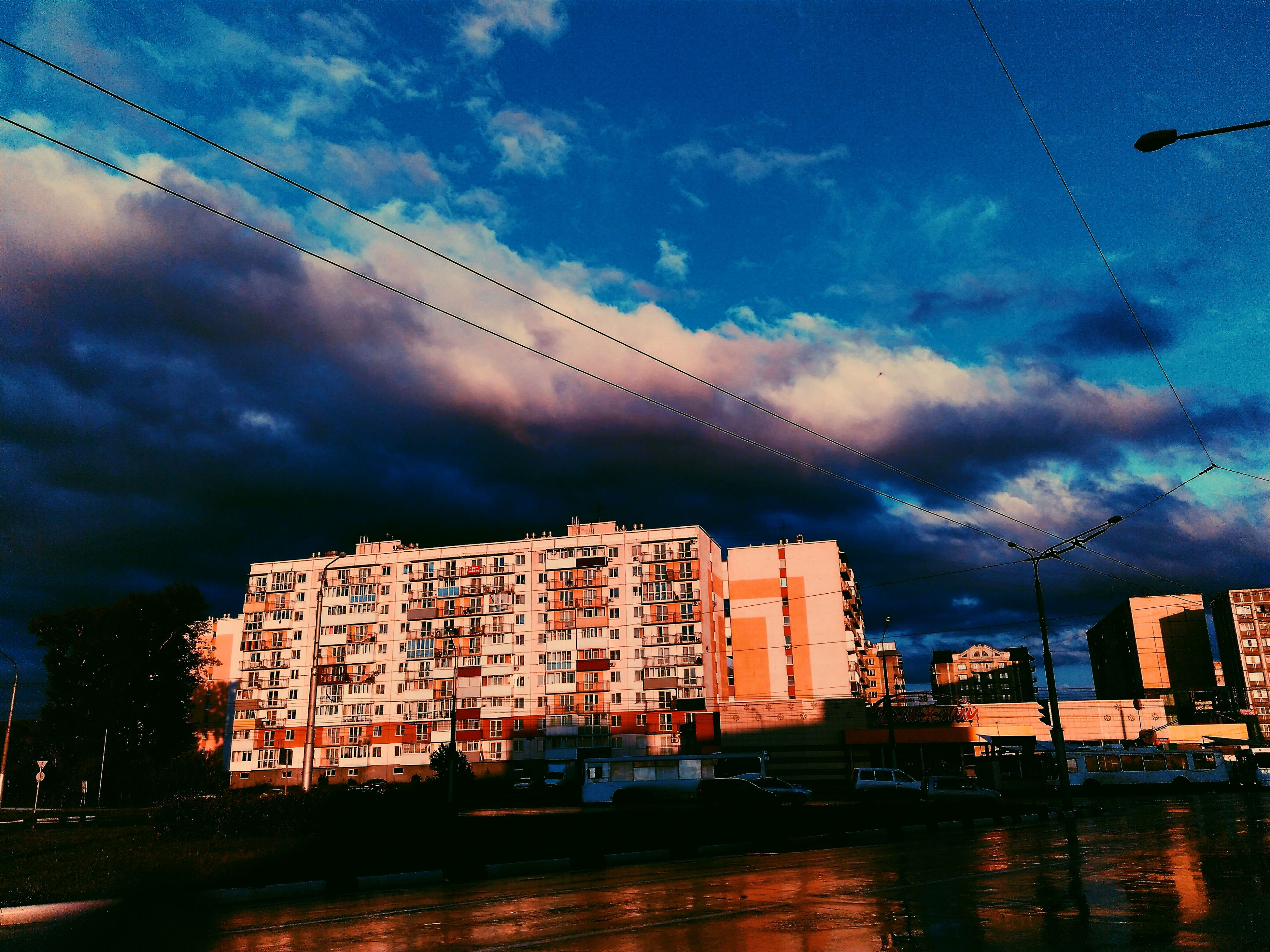 sky, architecture, built structure, cloud - sky, cloudy, city, dusk, weather, illuminated, cloud, building, outdoors, city life, no people, overcast, nature, cable, day