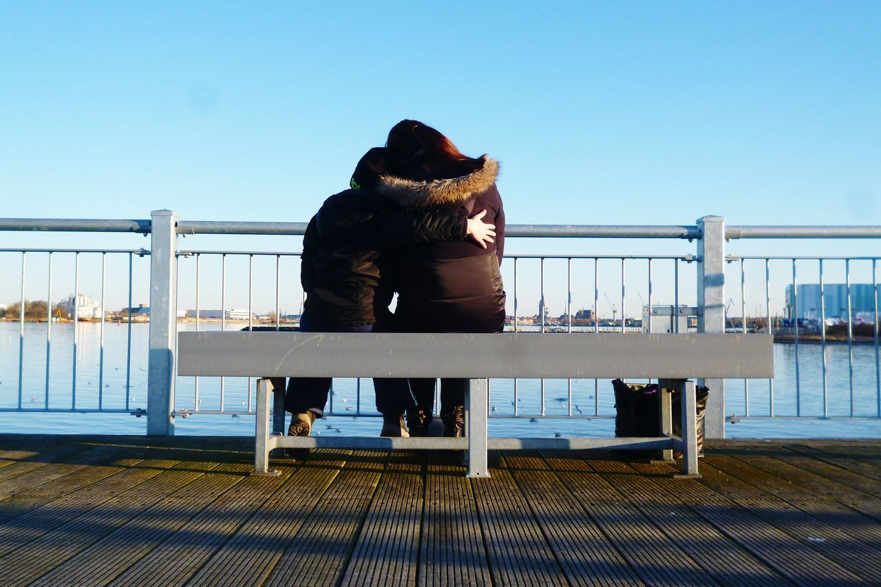 Rear View Of Mother And Son Sitting On Bench At Promenade