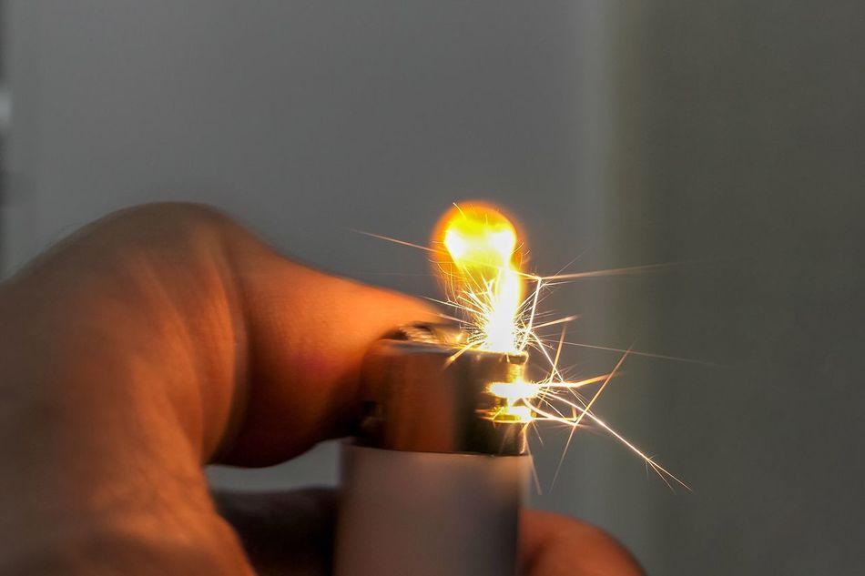Sprühende Funken beim Anzünden eines weissen Feuerzeuges - Funken Sprühen Fliegen Schießen Durch Die Luft Feuerzeug Weiss Gelb Orange Brennen Flamme Butan Gas Feuer Hitze Glühen Erleuchten Beleuchten Menschlicher Finger Menschliche Hand Licht Wärme überleben Element Energie
