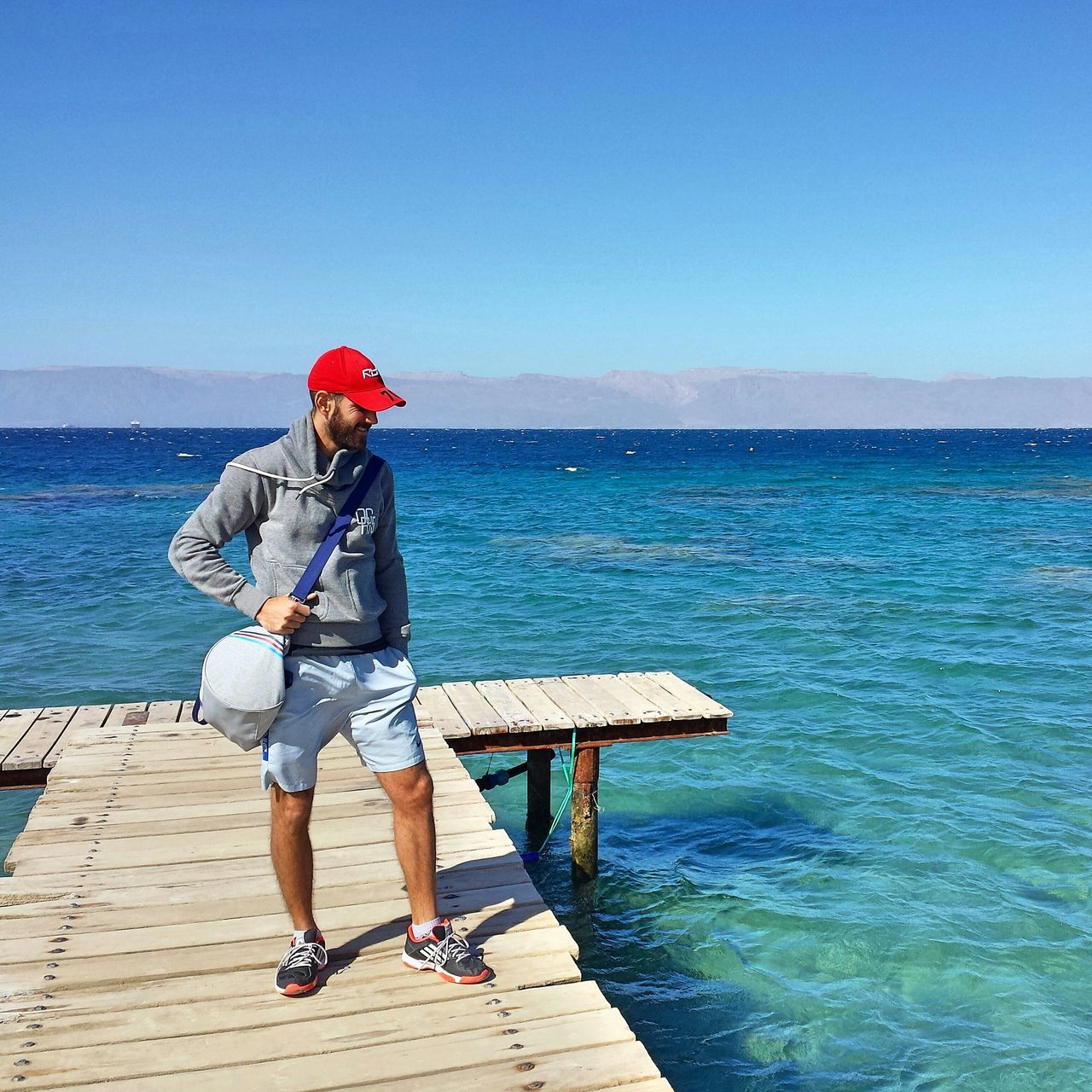water, full length, sea, one person, day, clear sky, nature, casual clothing, leisure activity, lifestyles, real people, outdoors, standing, tranquil scene, beauty in nature, blue, horizon over water, scenics, young adult, fishing pole, sky, people