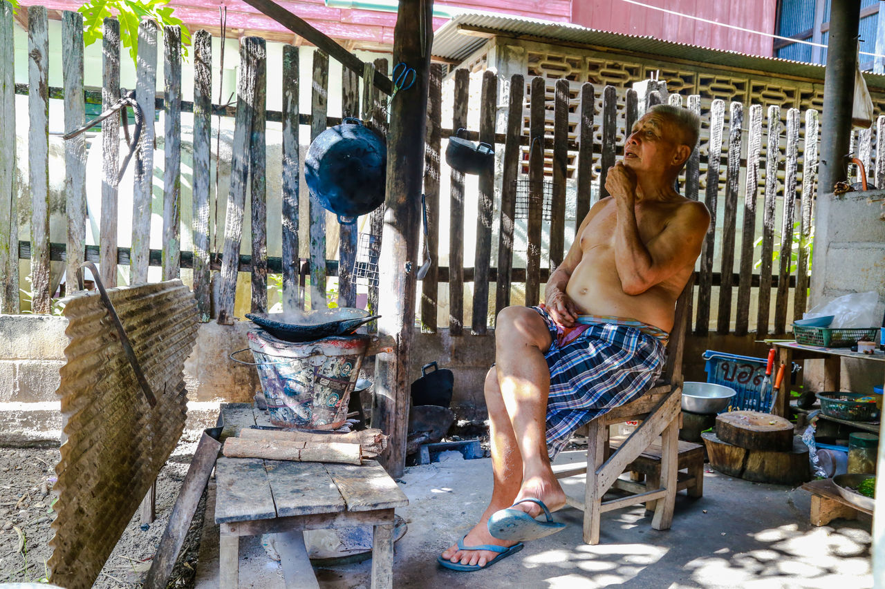 Old men are sitting at home cooking in Ban Hong is a district of Lamphun Province, northern Thailand. Cooking At Home Wait Adult Adults Only Day Elderly Man Full Length Occupation Old People, Man One Man Only One Person Only Men Outdoors People Real People Shirtless Sitting Workshop Young Adult