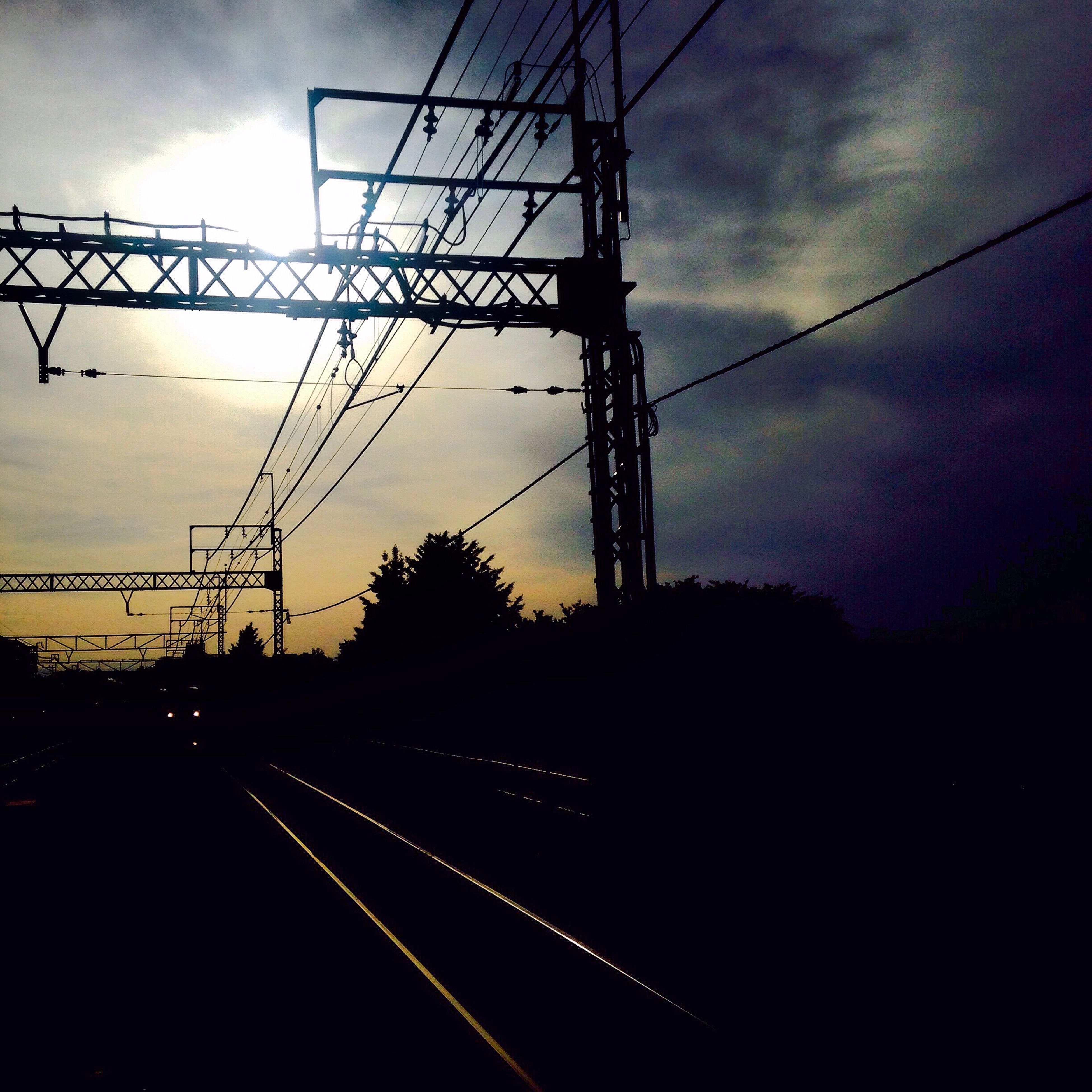 power line, electricity pylon, power supply, electricity, sunset, connection, sky, silhouette, cable, cloud - sky, fuel and power generation, technology, power cable, dusk, low angle view, transportation, railroad track, cloud, cloudy, no people