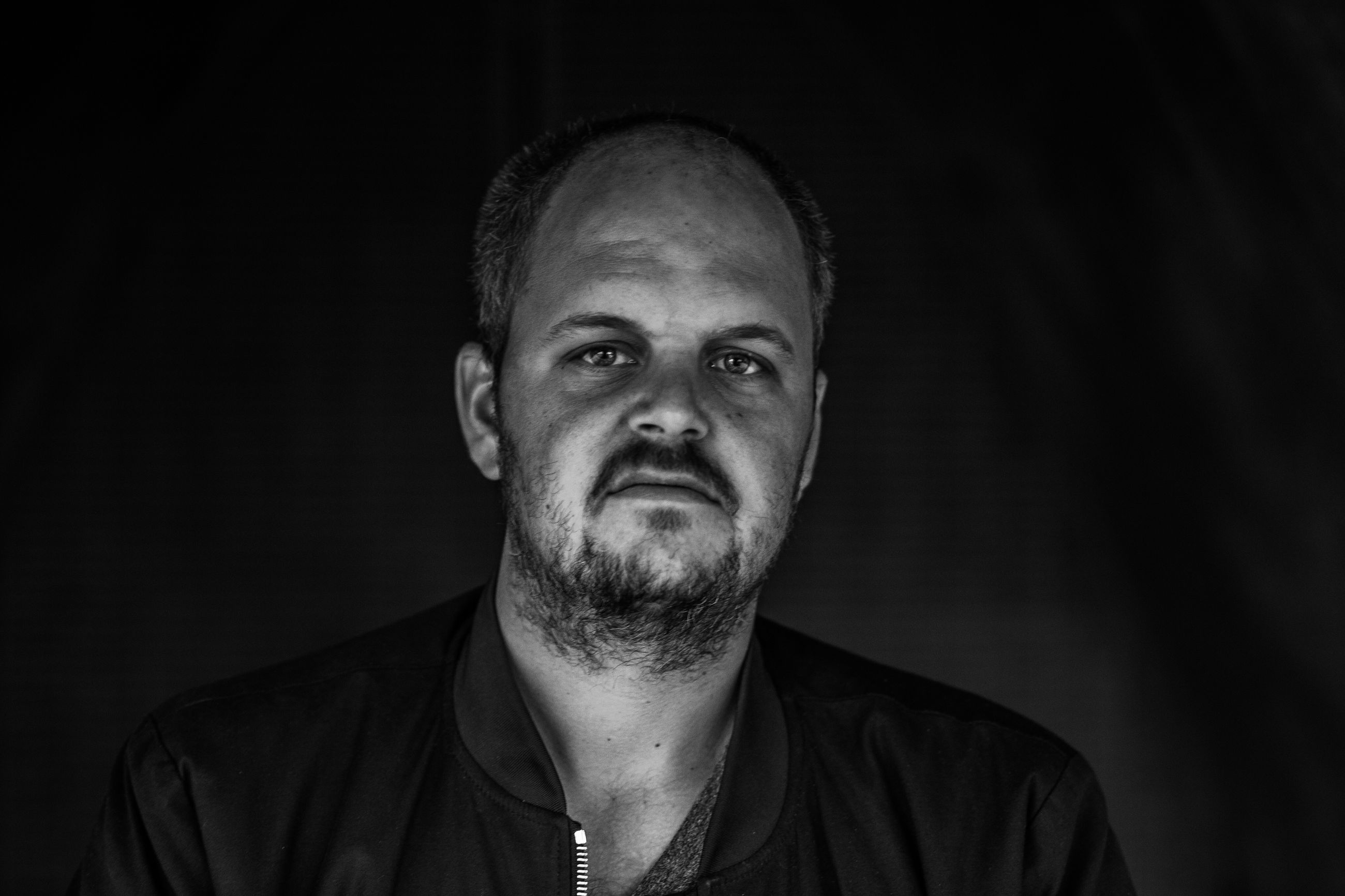 looking at camera, portrait, one person, black background, studio shot, front view, mid adult, headshot, real people, human face, close-up, only men, one man only, adults only, adult, people, indoors, human body part