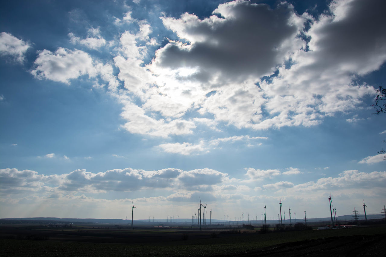 cloud - sky, environmental conservation, sky, fuel and power generation, wind turbine, renewable energy, wind power, alternative energy, day, no people, windmill, field, landscape, nature, outdoors, industrial windmill, scenics, beauty in nature, electricity pylon