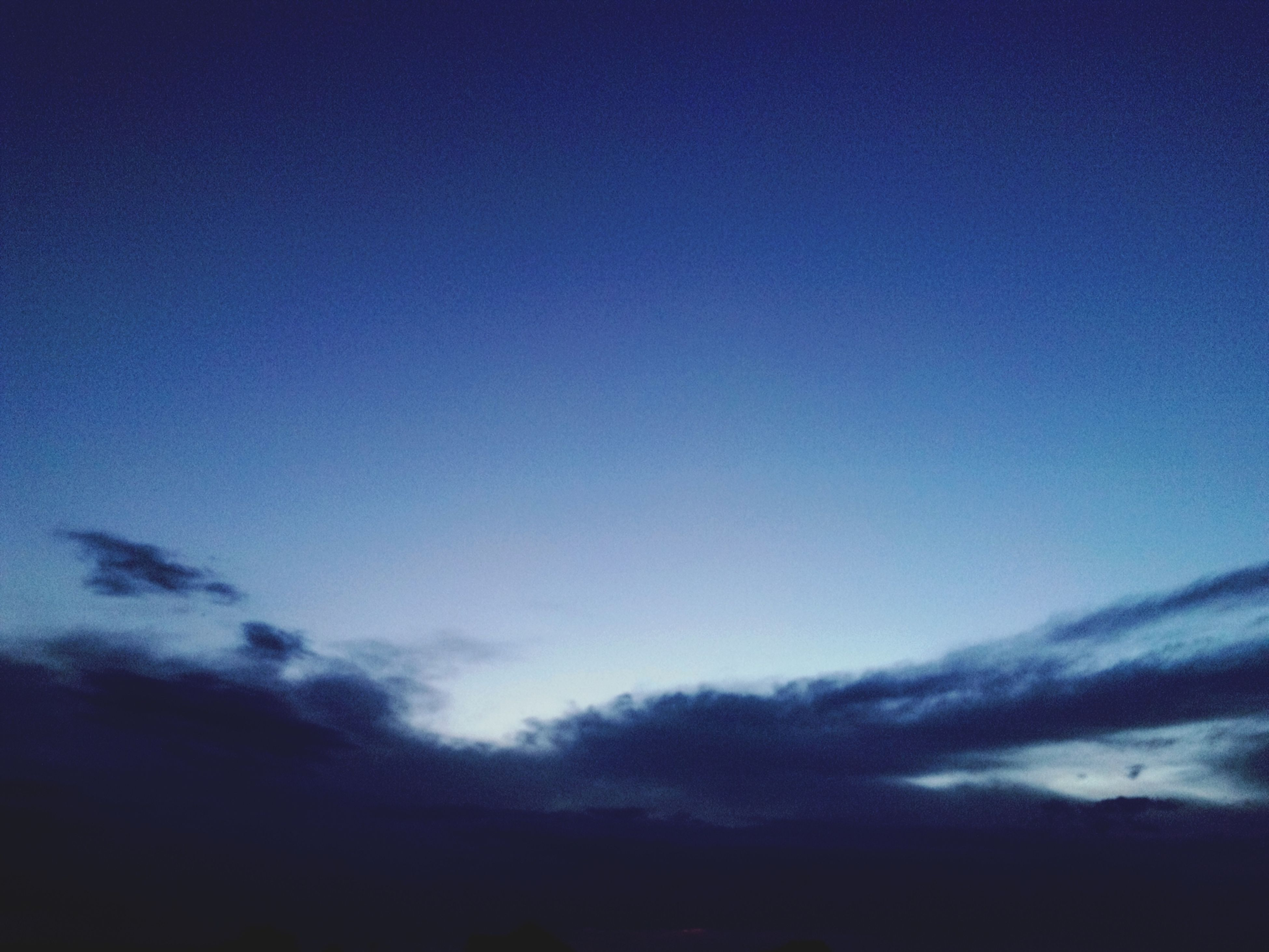 blue, scenics, beauty in nature, tranquility, tranquil scene, sky, copy space, nature, silhouette, low angle view, idyllic, cloud - sky, dusk, majestic, outdoors, cloudscape, cloud, no people, sunset, clear sky