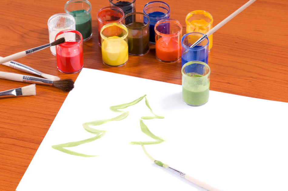 Many colorful paints in cans and brushes on table, Christmas tree painted on white paper sheet lying on wooden table, horizontal orientation, nobody. ArtWork Brush Brushes Can Cans Christmas Colorful Creativity Equipment Multicolored Multicoloured No People Objects Paint Painted Painting Paintings Paints Paper Paper Sheet Sheet Table Tree Xmas Xmas Tree
