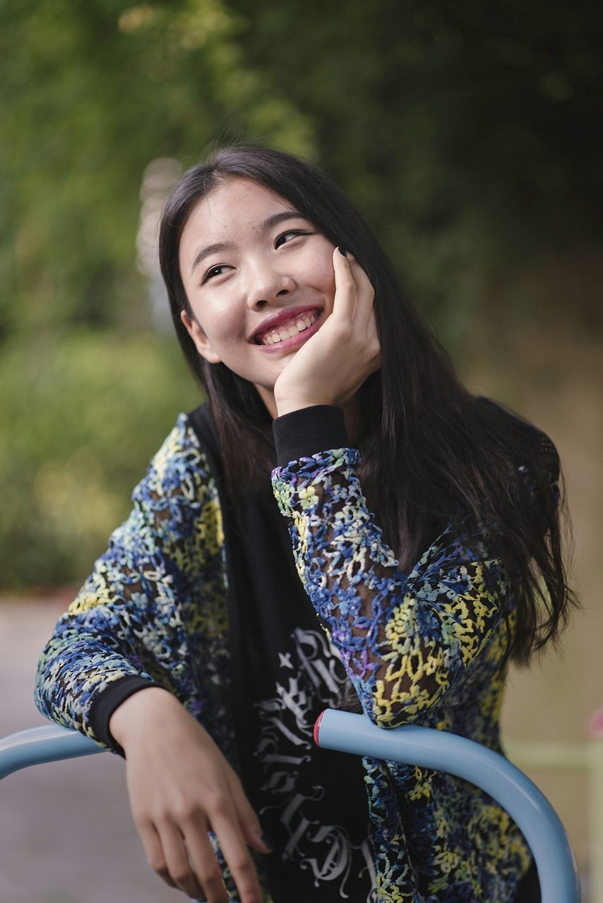 smiling, real people, lifestyles, one person, leisure activity, happiness, black hair, young adult, young women, casual clothing, outdoors, day, cheerful, tree, bicycle, nature