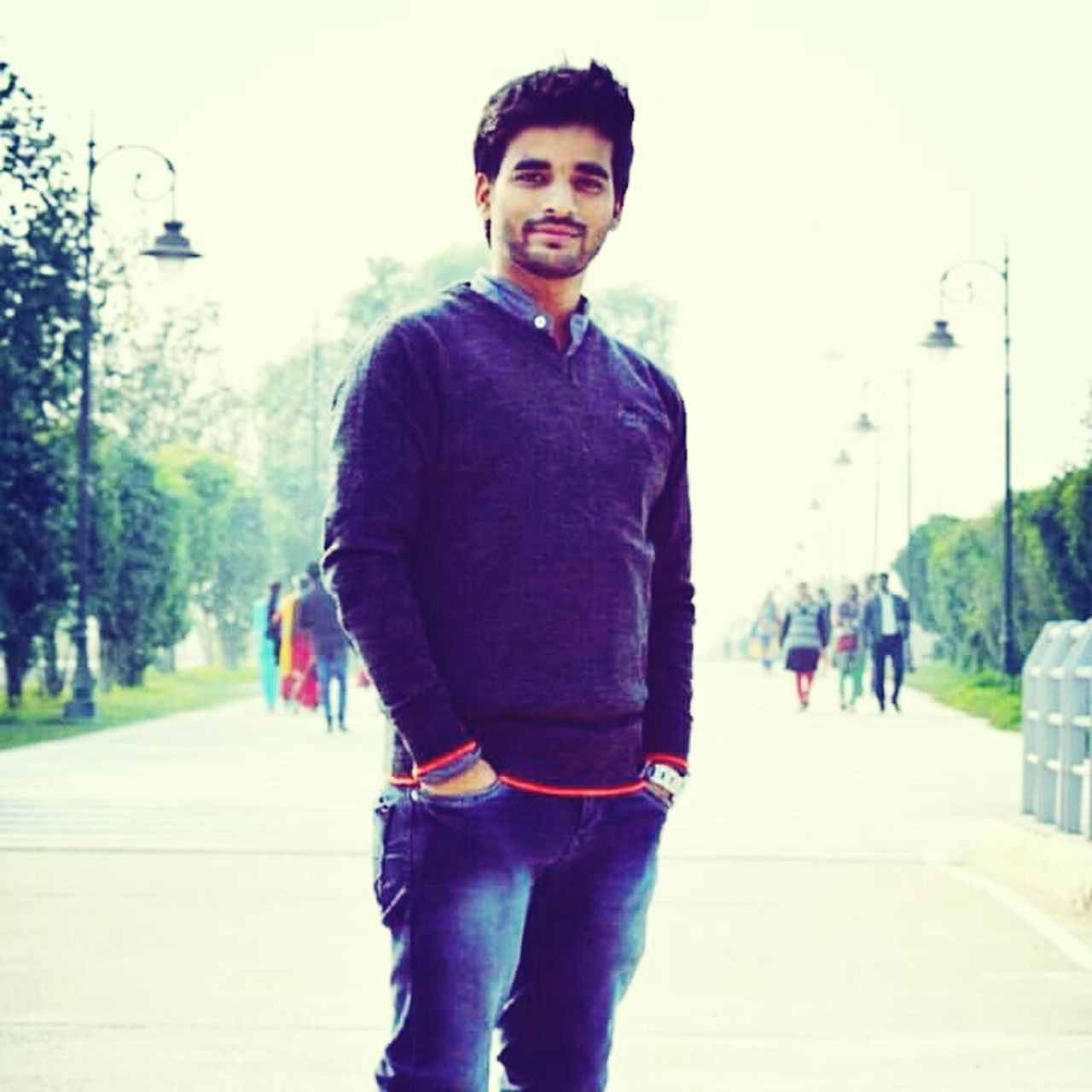looking at camera, smiling, portrait, real people, casual clothing, one person, happiness, young adult, standing, focus on foreground, hands in pockets, young men, outdoors, lifestyles, day, cheerful, tree, one man only, adult, people, adults only