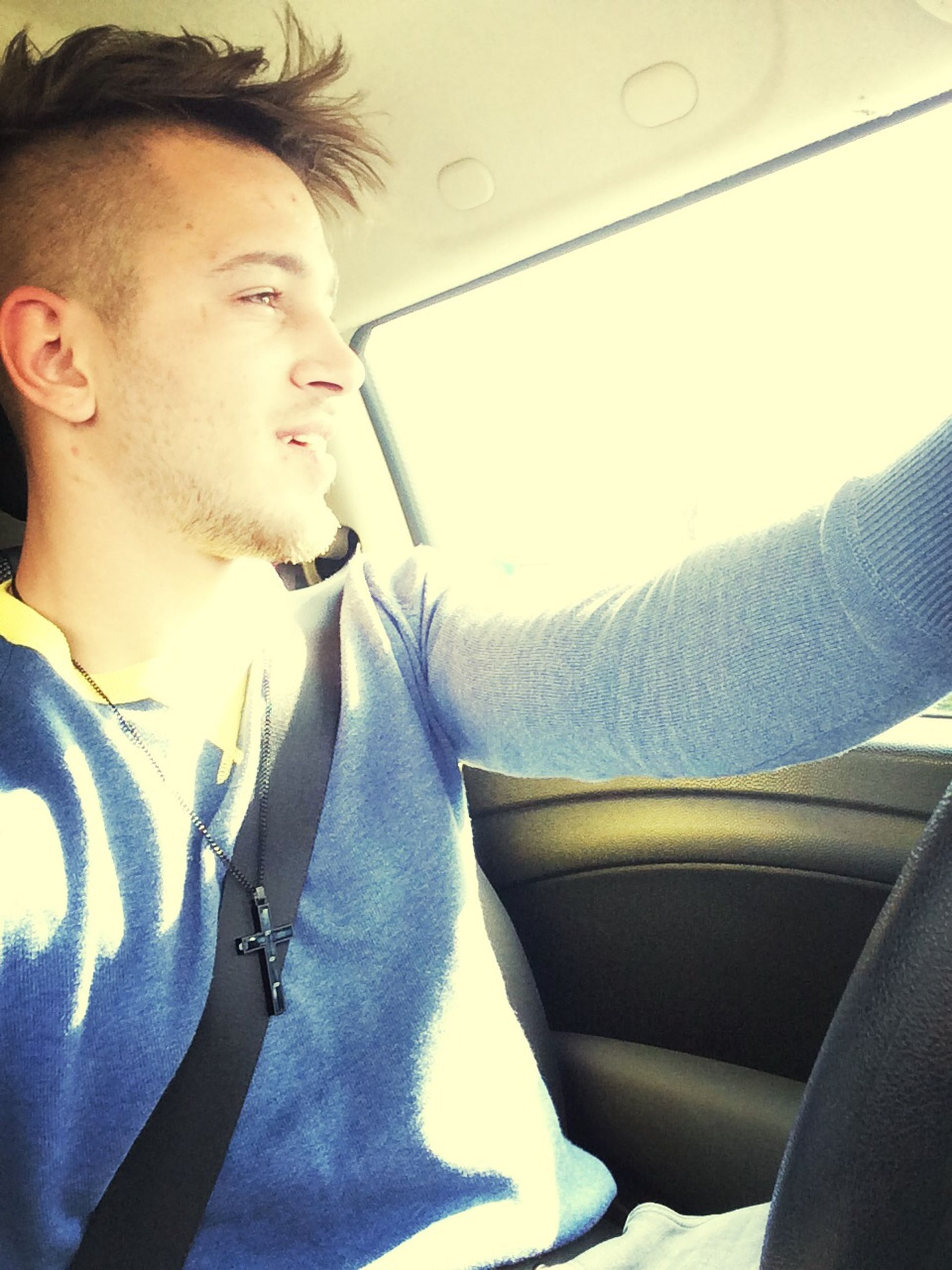indoors, vehicle interior, young adult, lifestyles, person, transportation, young men, leisure activity, mode of transport, headshot, portrait, looking at camera, sitting, car interior, relaxation, casual clothing, car, window