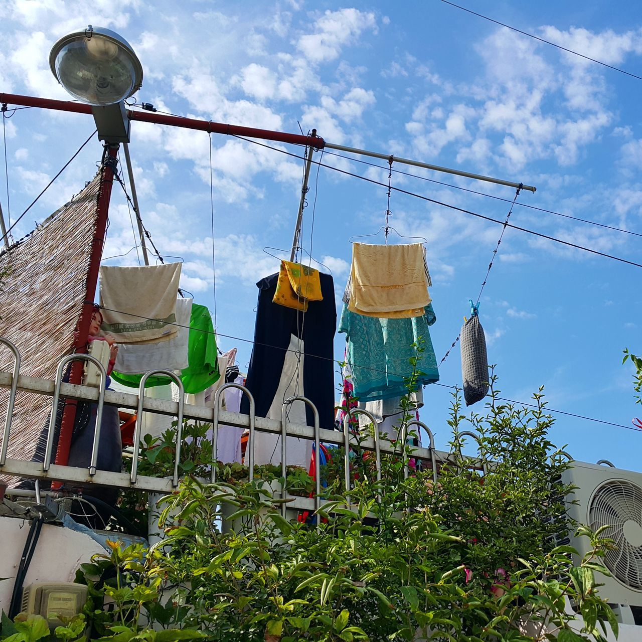 hanging, clothesline, sky, clothing, drying, laundry, building exterior, day, built structure, low angle view, architecture, outdoors, clothespin, no people, cloud - sky, growth, city
