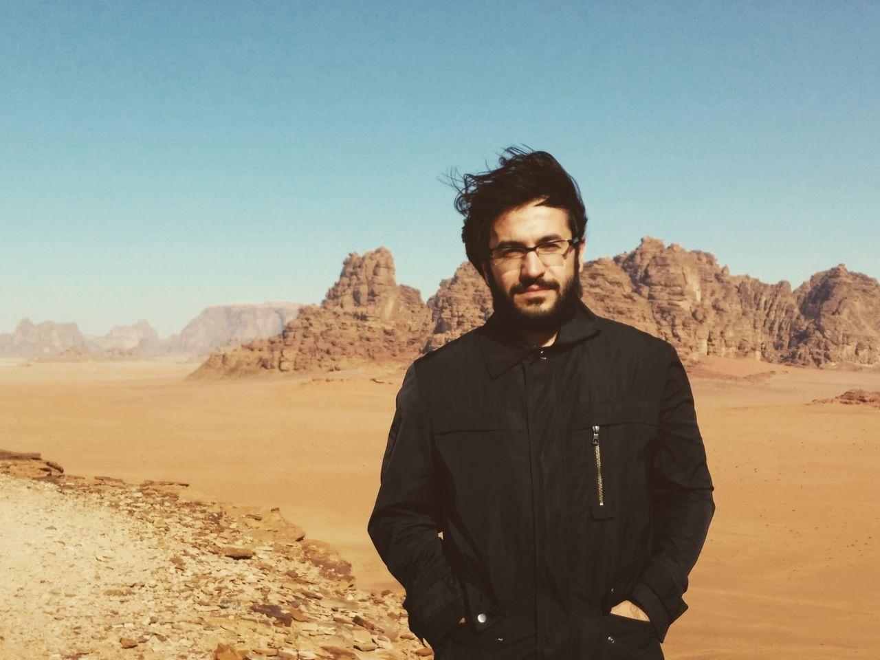 Portrait Of Man At Desert Against Clear Blue Sky