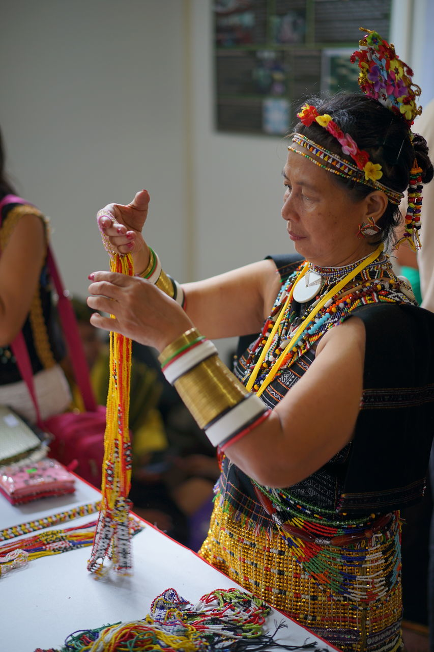 traditional clothing, real people, cultures, holding, celebration, one person, indoors, tradition, traditional dancing, lifestyles, skill, standing, occupation, day, young adult, close-up