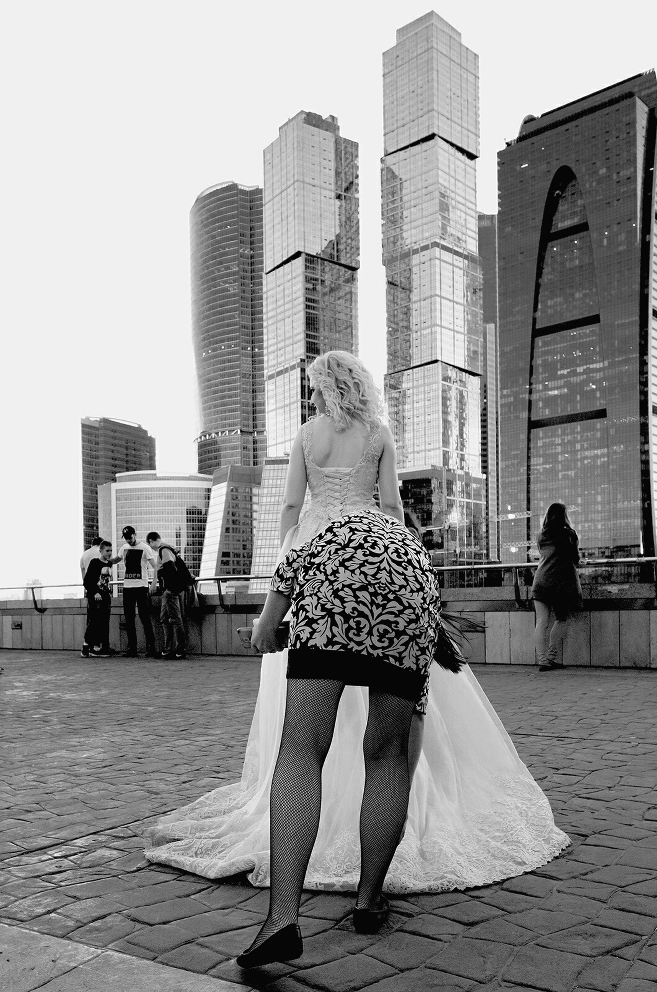 real people, built structure, building exterior, architecture, outdoors, leisure activity, women, lifestyles, fashion, rear view, day, city, full length, clear sky, large group of people, modern, glamour, fashion show, fashion model, skyscraper, sky, people