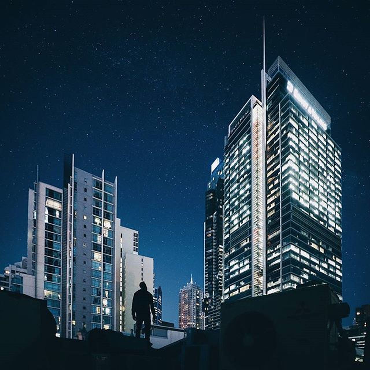 architecture, night, built structure, real people, building exterior, lifestyles, low angle view, skyscraper, men, one person, sky, outdoors, city, star - space, illuminated, silhouette, leisure activity, astronomy, modern, people, adult, adults only, one man only, only men