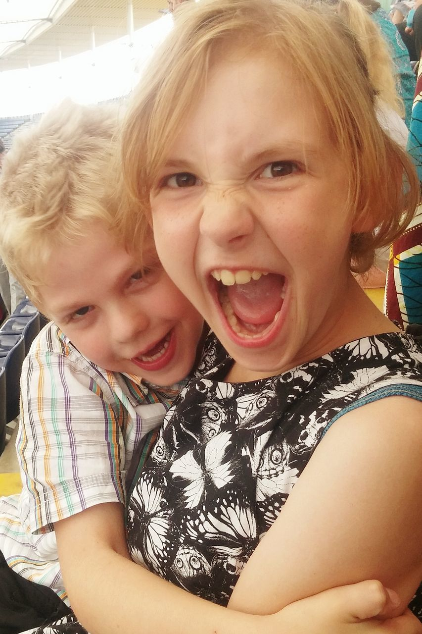 Portrait Of Smiling Siblings Embracing While Sitting At Stadium