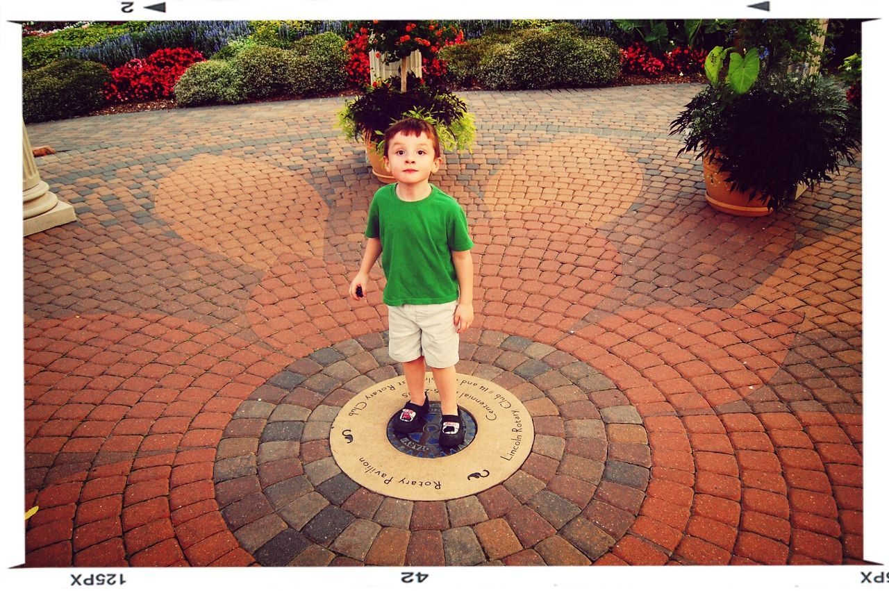 Full Length Portrait Of Cute Boy Standing On Paving Stone In Park