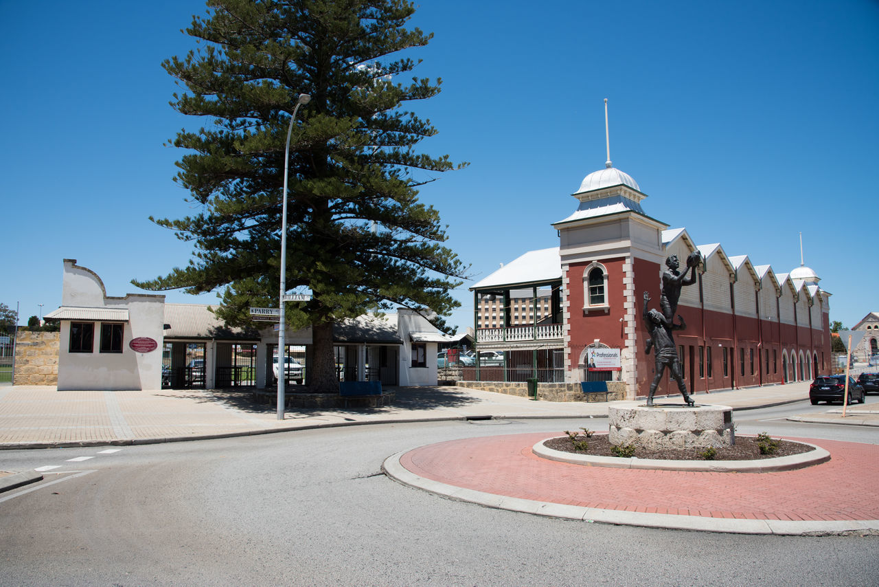 Round about with sculpture, Fremantle Oval entrance and architecture in downtown historic Fremantle, Western Australia. Architecture Blue Brick Building Exterior Built Structure City Entrance Fremantle  Fremantle Oval Limestone Norfolk Pines Outdoors Oval Road Round About Sculpture Sky Sports Venue Street Sunny Tourism Tourist Attraction  Tree Venue Western Australia