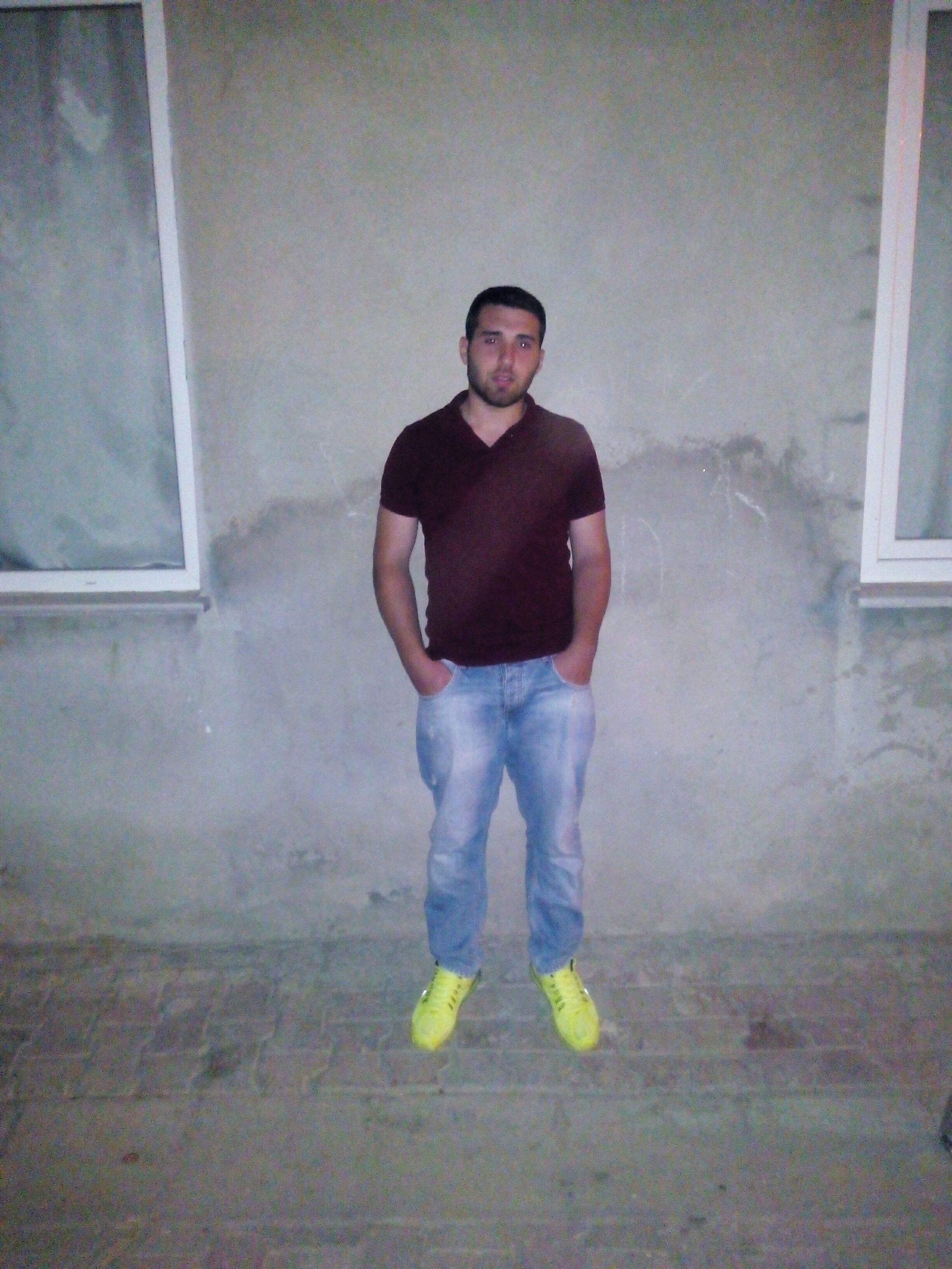 young adult, casual clothing, lifestyles, person, looking at camera, portrait, front view, standing, leisure activity, young men, full length, wall - building feature, indoors, three quarter length, holding, architecture, built structure