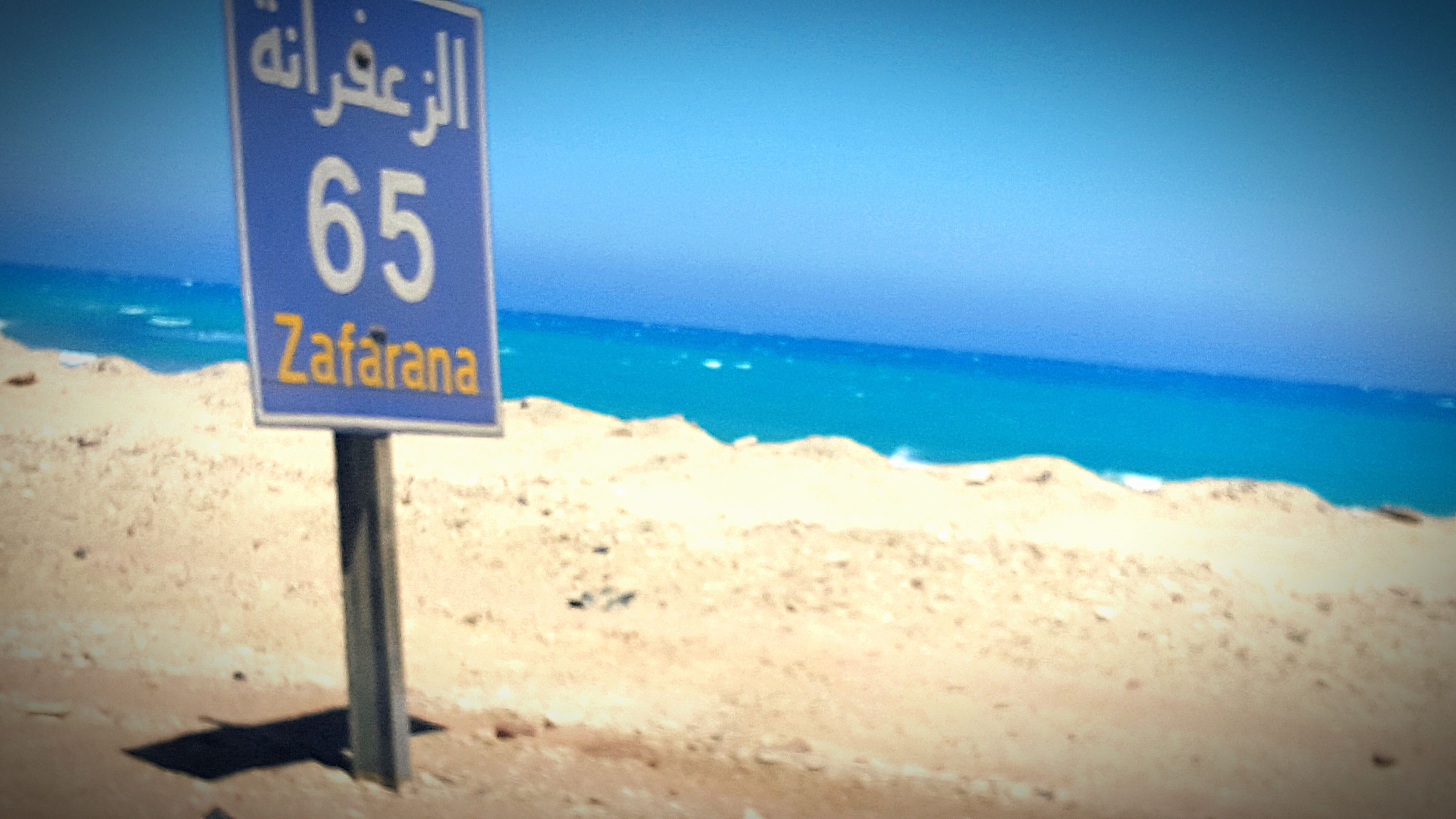 sea, text, horizon over water, western script, communication, beach, guidance, water, blue, shore, sign, information sign, sand, clear sky, copy space, tranquil scene, tranquility, warning sign, capital letter, scenics