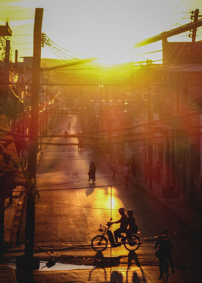 Architecture Built Structure City Cuba Leisure Activity Lifestyles Medium Group Of People Mode Of Transport Orange Color Outdoors Parked Santa Clara Sky Stationary Street Sun Sunbeam Sunlight Sunset The Way Forward Unrecognizable Person