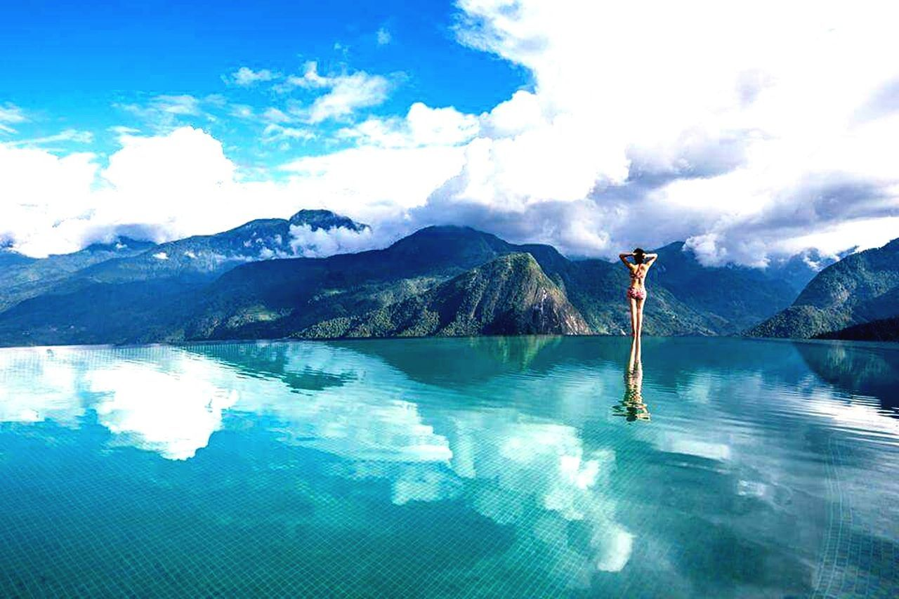 water, mountain, one person, swimming pool, real people, scenics, beauty in nature, day, standing, outdoors, full length, nature, sky, leisure activity, blue, lifestyles, people