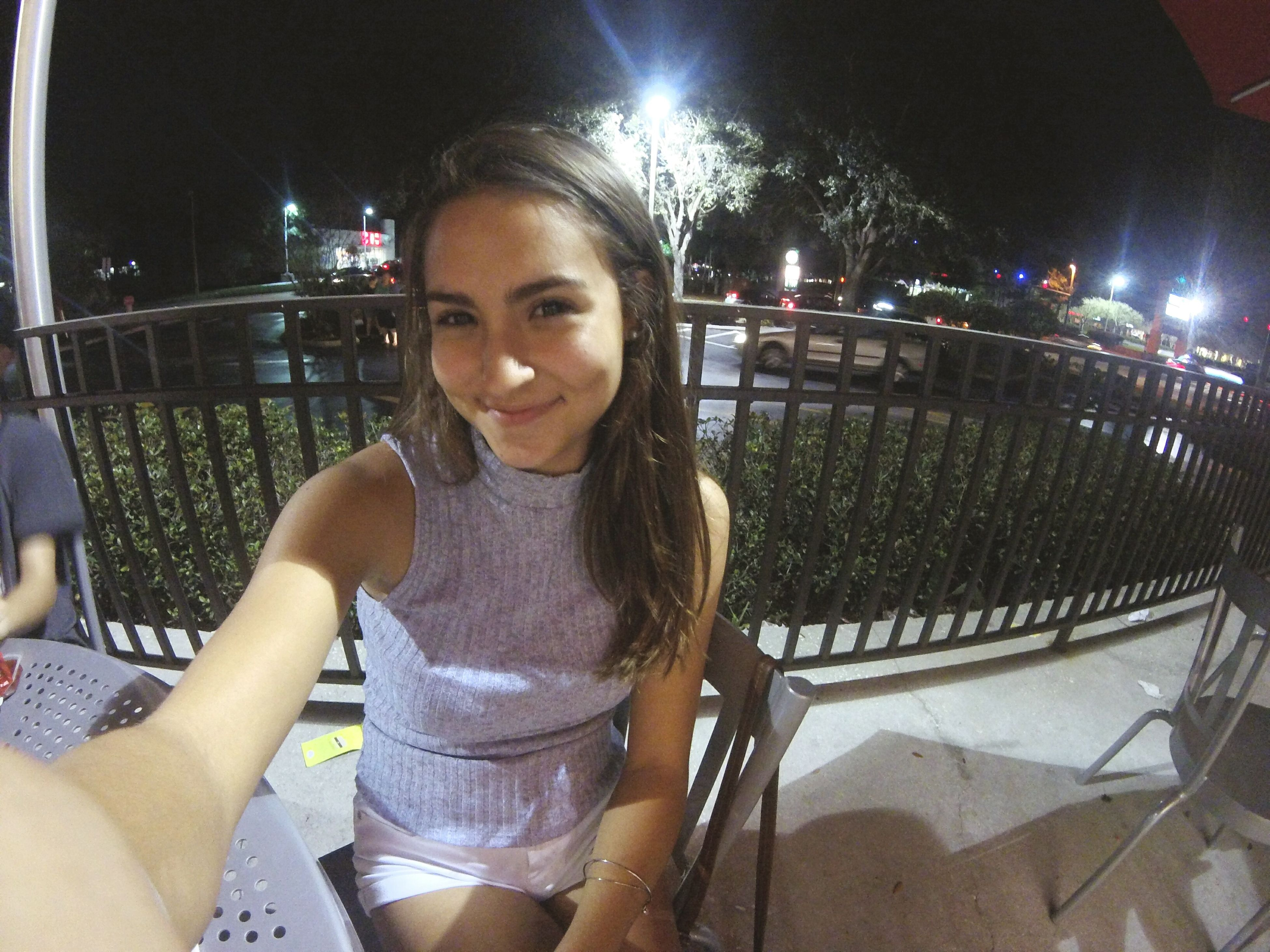 lifestyles, leisure activity, night, person, looking at camera, illuminated, portrait, casual clothing, young adult, indoors, front view, standing, young women, sitting, headshot, happiness, waist up, smiling