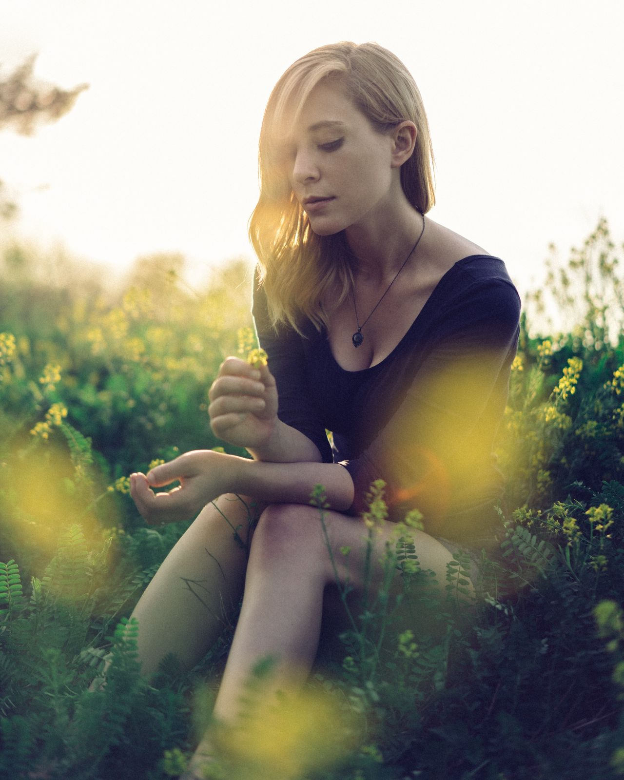 Young Adult One Person Young Women Sitting Three Quarter Length Holding Real People Casual Clothing Field Grass Outdoors Lifestyles Bad Habit Blond Hair Day Nature Tree People Adult May