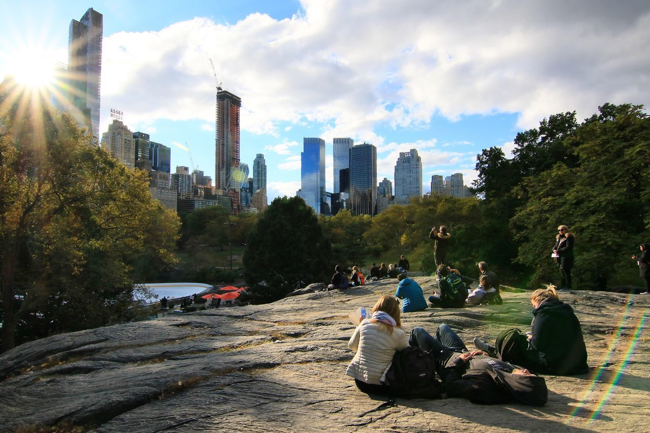 Chilling out in Central Park, NYC Real People Leisure Activity Tree Building Exterior Built Structure Architecture Lifestyles Sky City Day Women Nature Growth Men Beauty In Nature Skyscraper Outdoors Cloud - Sky Large Group Of People City Beauty In Nature Sun lifeRock Formationban Life] Rock formaSunbeamnbeam