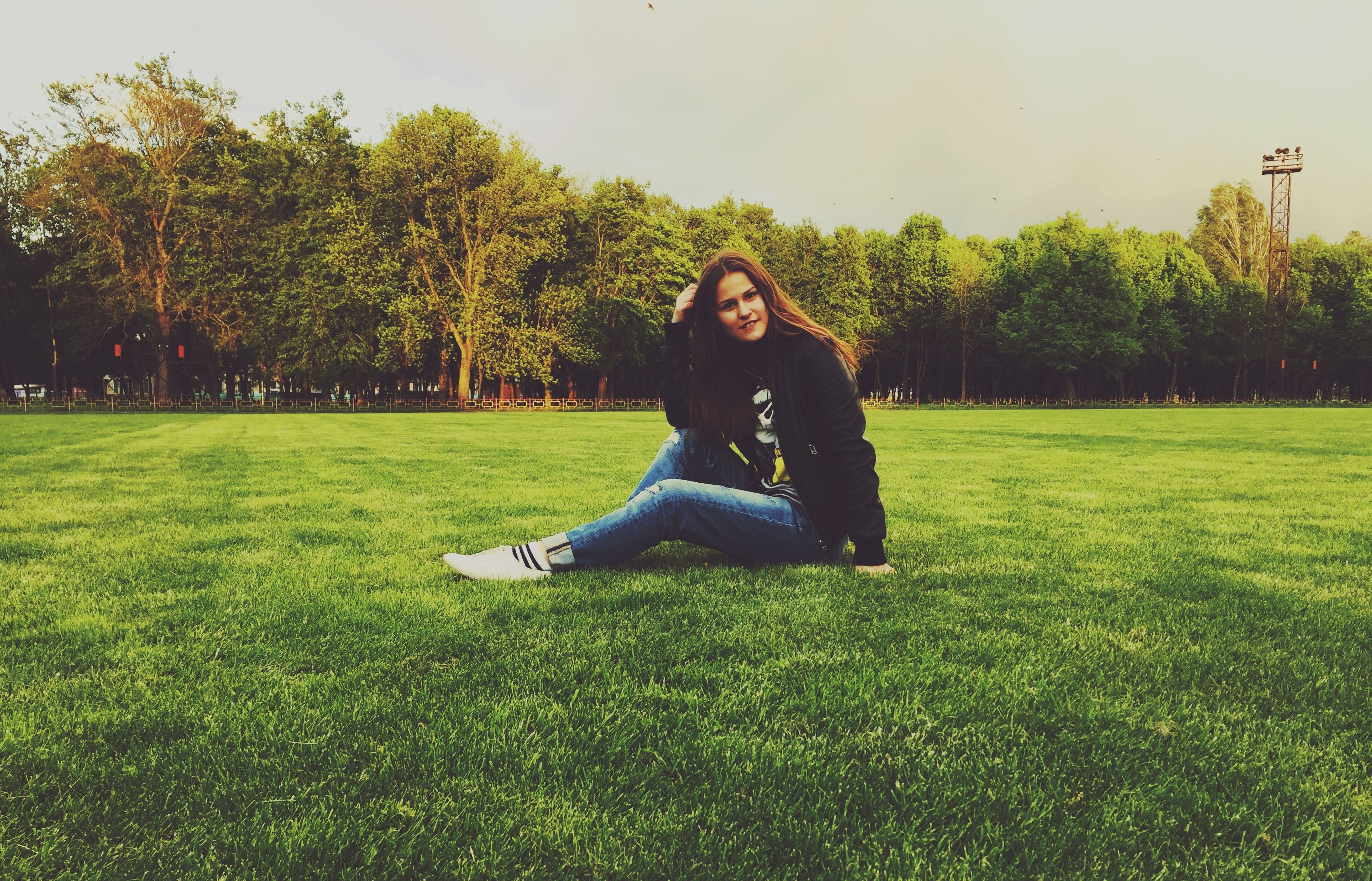 grass, young adult, lifestyles, person, leisure activity, full length, young women, tree, casual clothing, sitting, park - man made space, looking at camera, portrait, smiling, grassy, field, green color, happiness