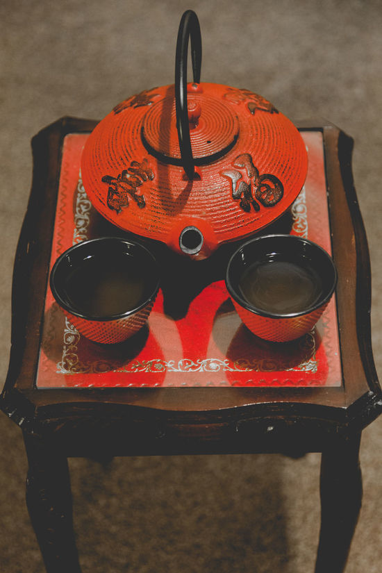 Japanese red cast iron tea pot with two cups full of tea on red small table in dark room Break Cast Iron Contrasting Colors Couple Dark Duotone Fit Free Time High Angle View Indoors  Love Melancholy Pair Pot Red Room Small Strong Shadow Table Tea Time Always Be Cozy