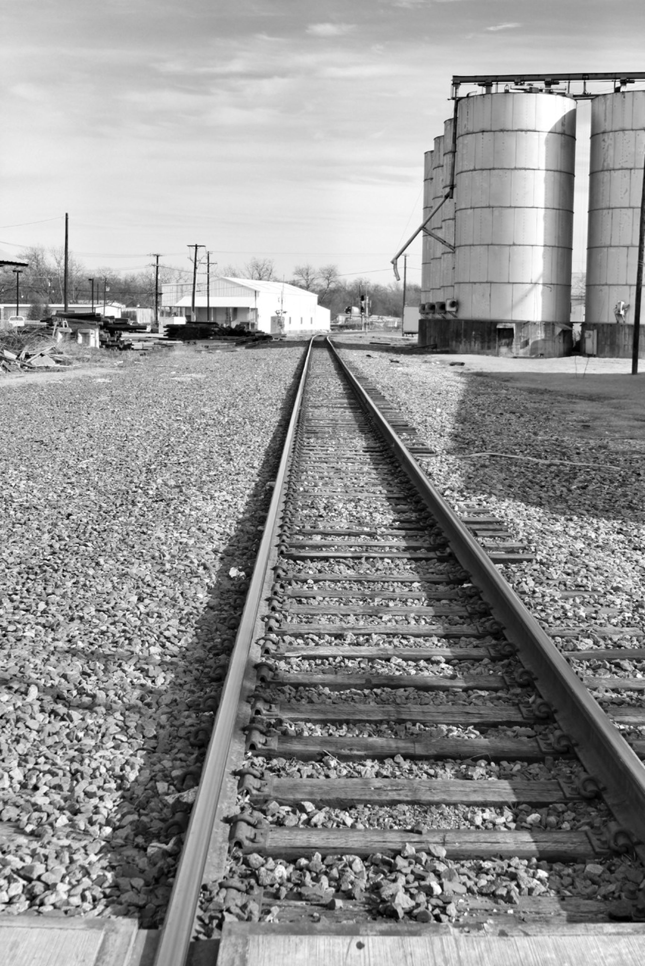railroad track, rail transportation, the way forward, transportation, diminishing perspective, sky, vanishing point, built structure, architecture, public transportation, cloud - sky, building exterior, railroad station platform, railway track, railroad station, surface level, day, outdoors, cloud, straight