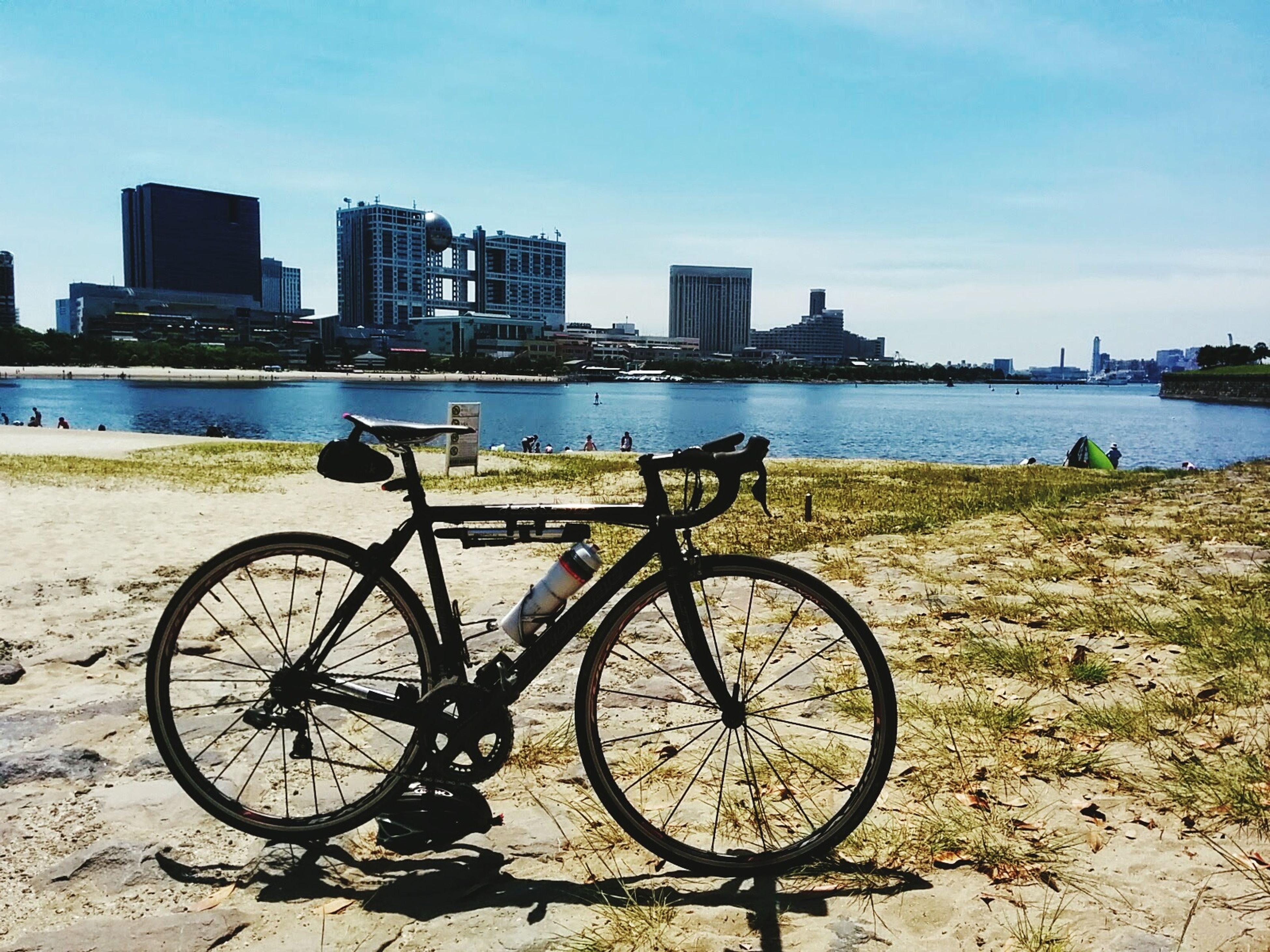 bicycle, transportation, mode of transport, land vehicle, stationary, parking, parked, water, sky, architecture, built structure, building exterior, outdoors, river, day, travel, no people, cycle, sea, leaning