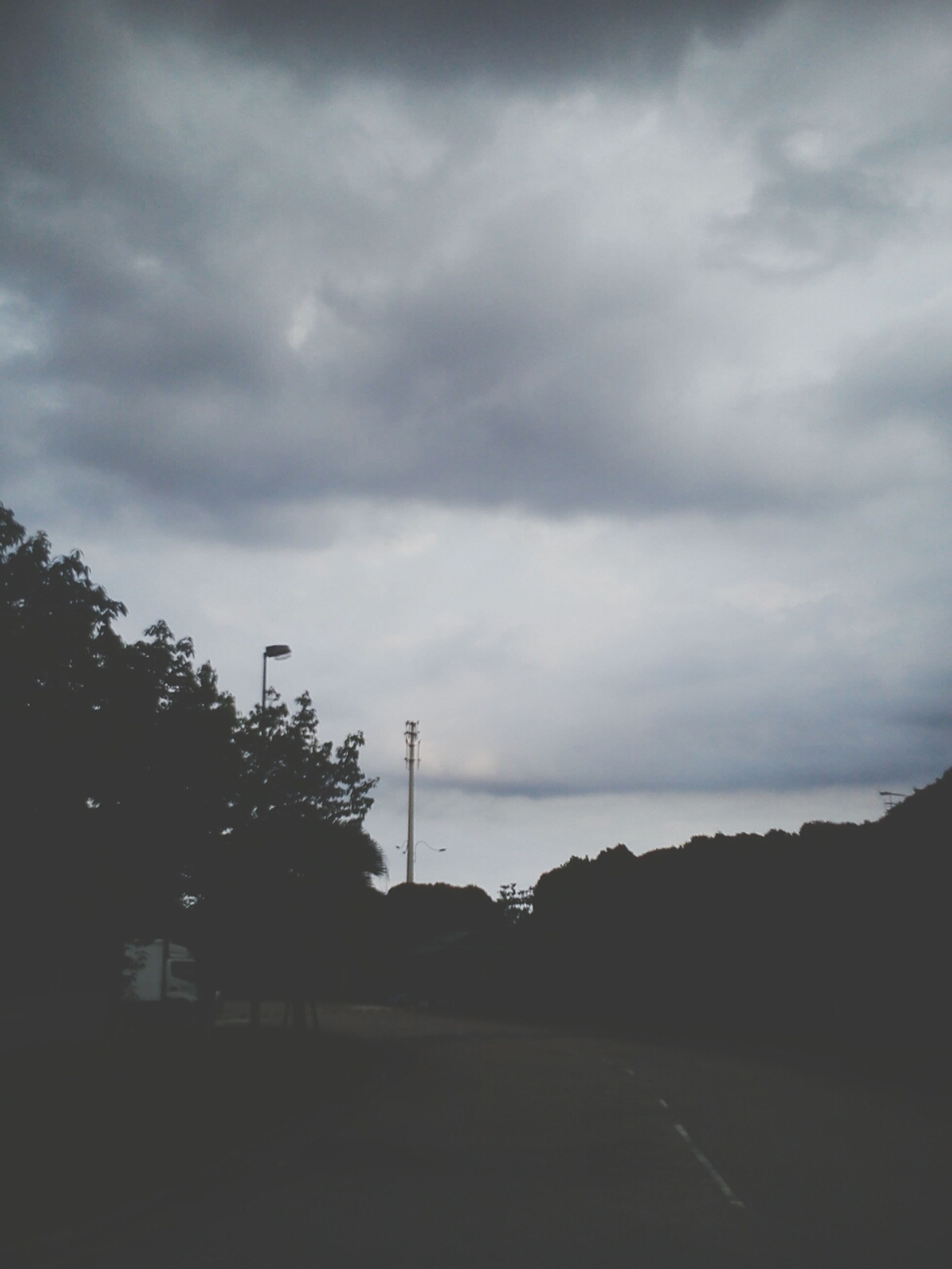 sky, cloud - sky, cloudy, overcast, silhouette, road, weather, cloud, tranquility, dusk, tree, storm cloud, tranquil scene, nature, the way forward, landscape, street, scenics, outdoors, beauty in nature