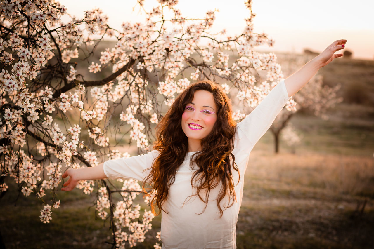 Carmen Almond Tree Almond Tree Blossom Backlight Beauty Blooming Casual Clothing Focus On Foreground Front View Happiness Leisure Activity Lifestyles Long Hair Looking At Camera Medium-length Hair Person Portrait Smiling Standing Three Quarter Length Young Adult Young Women
