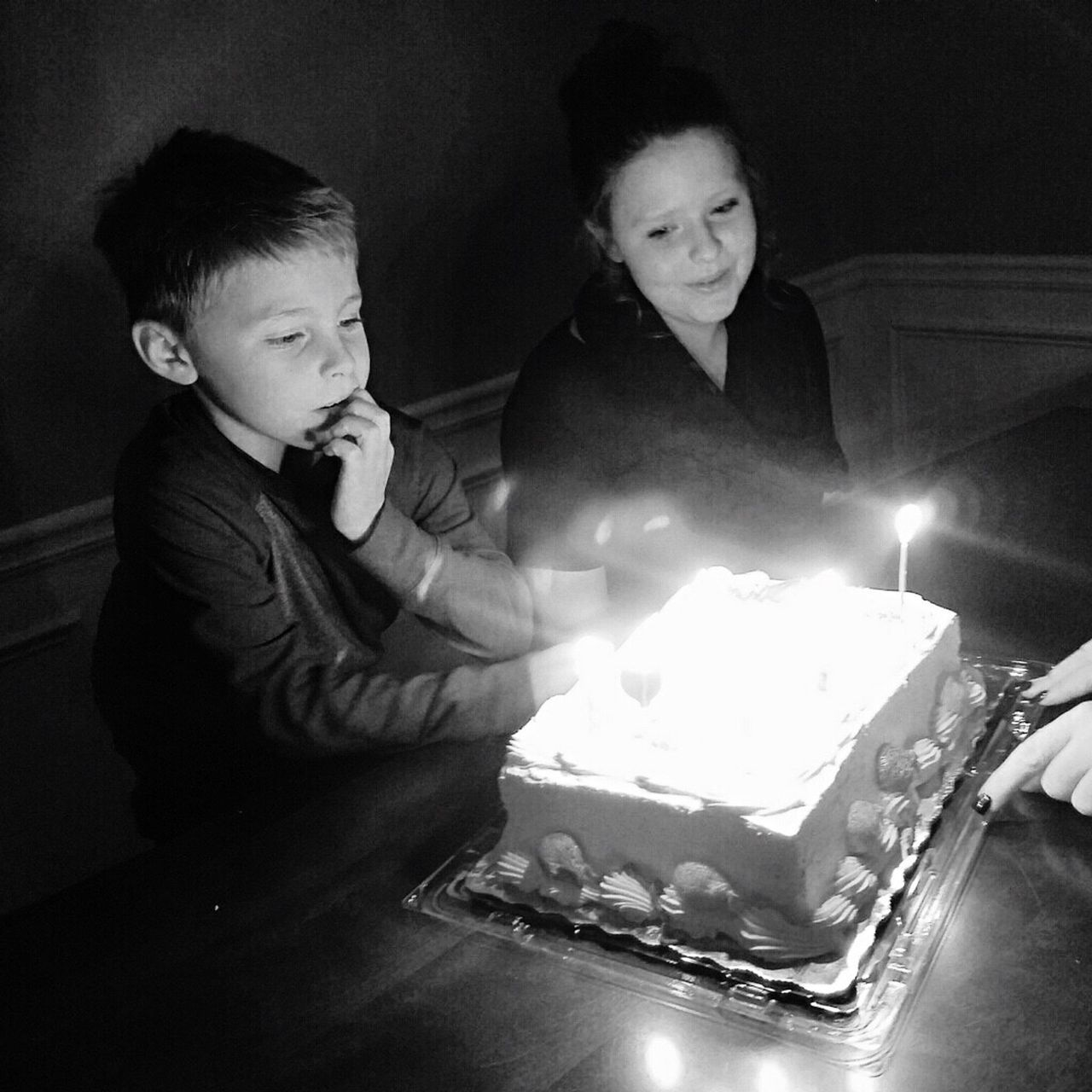 High Angle View Of Brother And Sister By Birthday Cake At Home