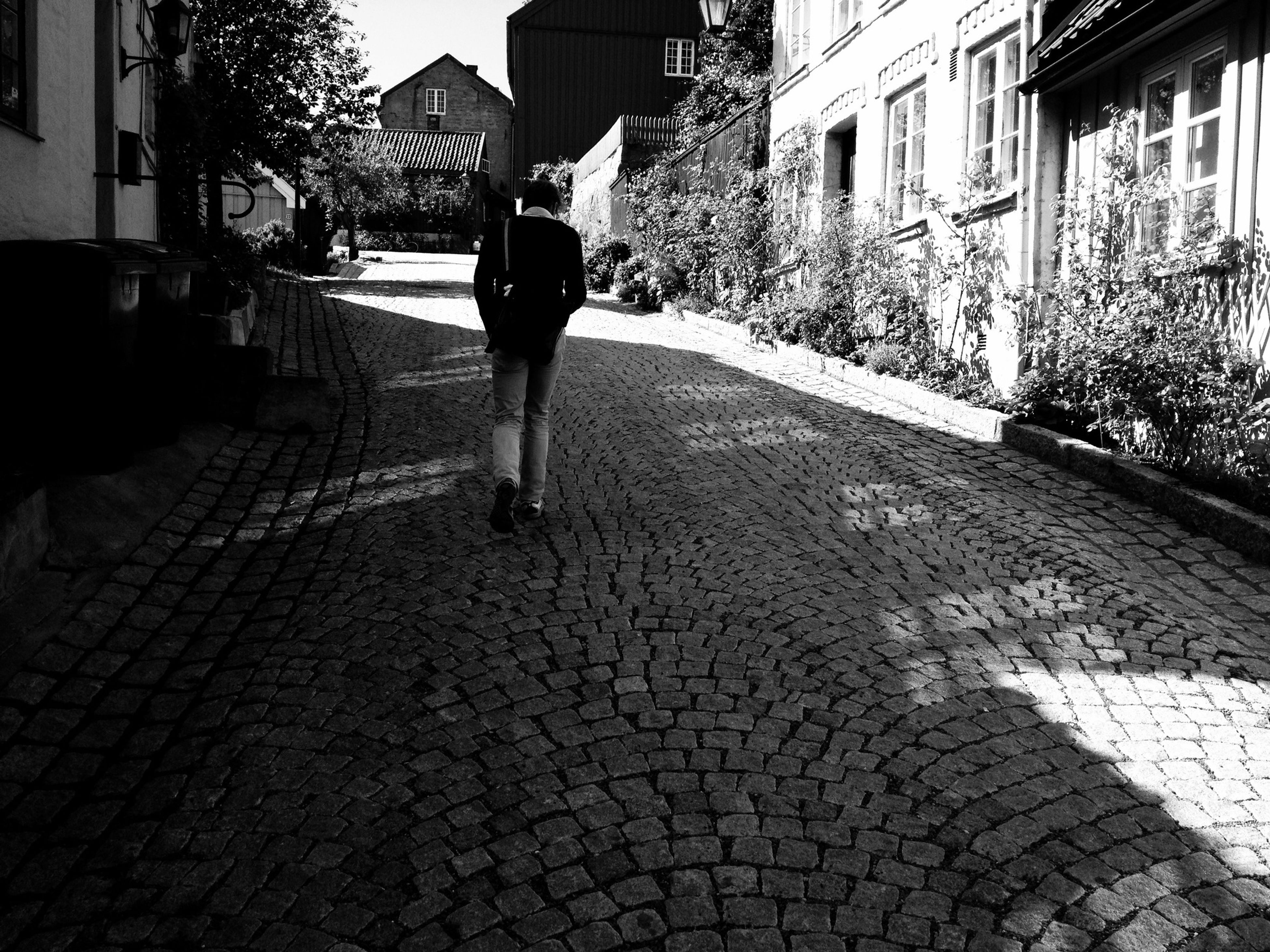building exterior, architecture, built structure, cobblestone, walking, lifestyles, the way forward, street, rear view, full length, person, men, leisure activity, city, footpath, paving stone, sunlight, walkway
