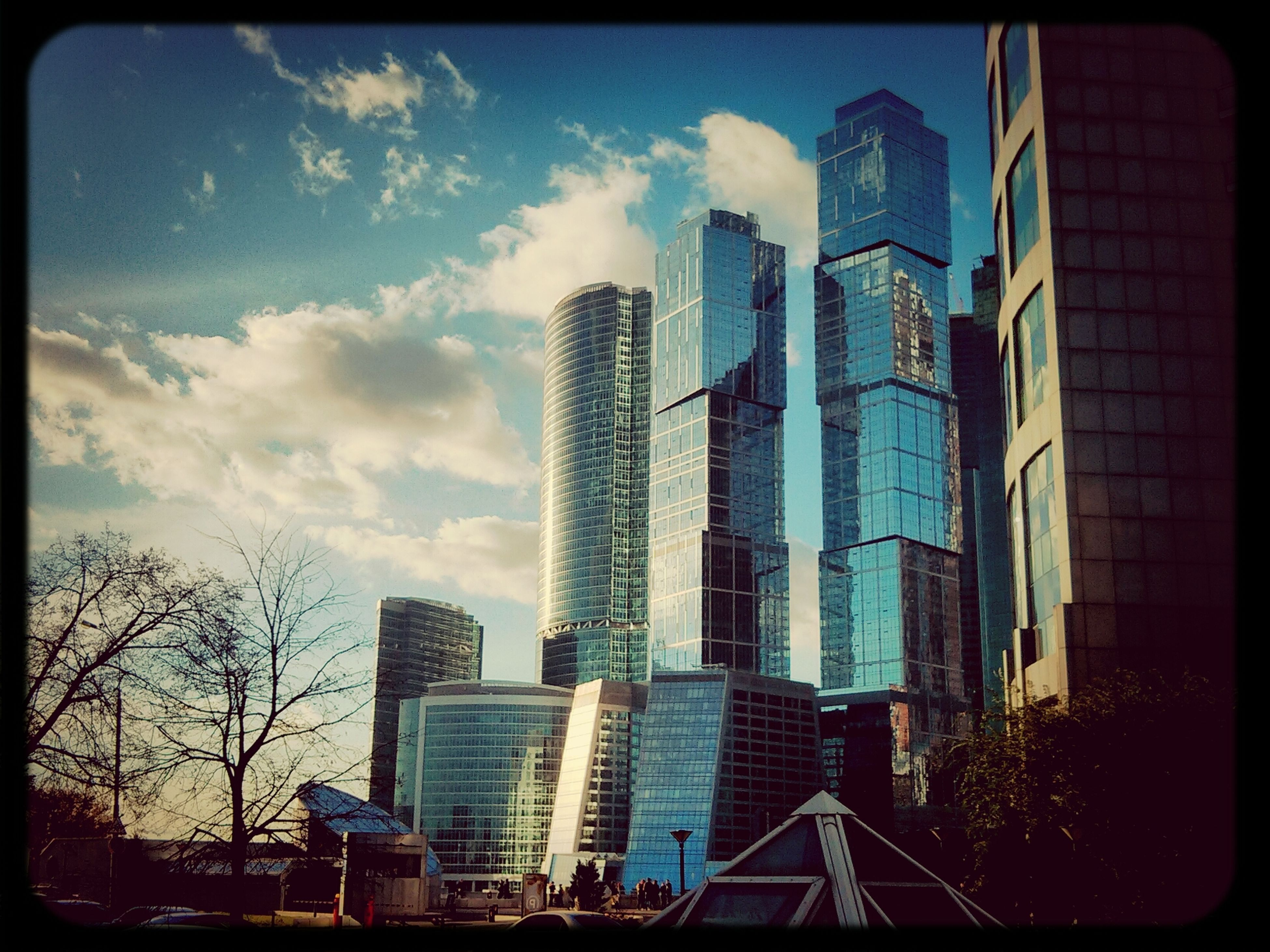 building exterior, architecture, built structure, transfer print, skyscraper, city, modern, office building, sky, tall - high, auto post production filter, tower, low angle view, building, cloud - sky, glass - material, cloud, tall, tree, city life