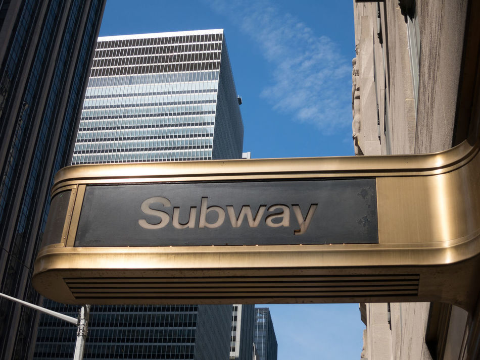 Entrance to NYC Subway in midtown Manhattan with blue skies and tall skyscrapers in the background. Architecture Building Exterior Built Structure Day Daytime Façade Gold Midtown Manhattan New York City No People NYC NYC Photography Outdoors Sign Skyscraper Skyscrapers In The Clouds Subway Subway Station Subway Station Sign Travel Travel Destinations