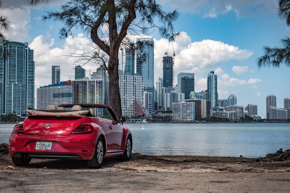 🚗🏙 City Architecture Building Exterior Transportation Skyscraper Built Structure Car Outdoors Red Cityscape Urban Skyline Cloud - Sky Mode Of Transport Land Vehicle Travel Destinations Modern Road Day Sky Water