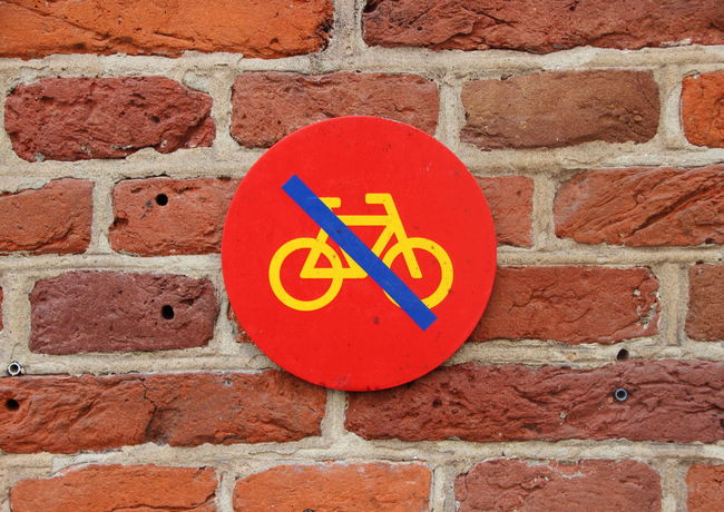 Bicycle Sign Blue Brick Wall Circle Close-up Communication Day Geometric Shape Guidance No Parking Sign No People Outdoors Paving Stone Red Representation Road Sign Stone Material Symbol
