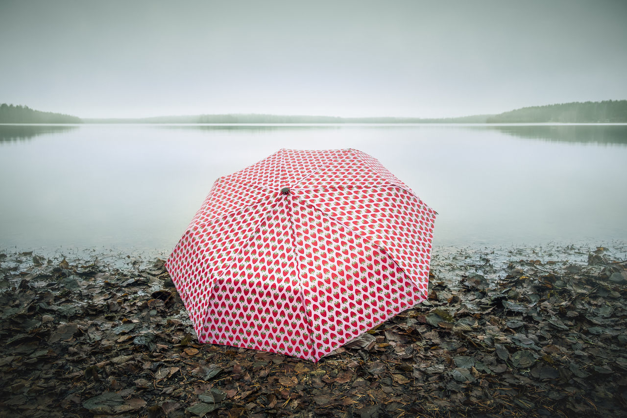 Pinky umbrella in the beach Autumn Beach Day Fall Floating On Water Fog Foggy Global Warming Gloomy Gloomy Weather Green Horizon Horizon Over Water Lake Light Mist Misty Nature Outdoors Pink PINKY Tranquil Scene Tranquility Umbrella Water