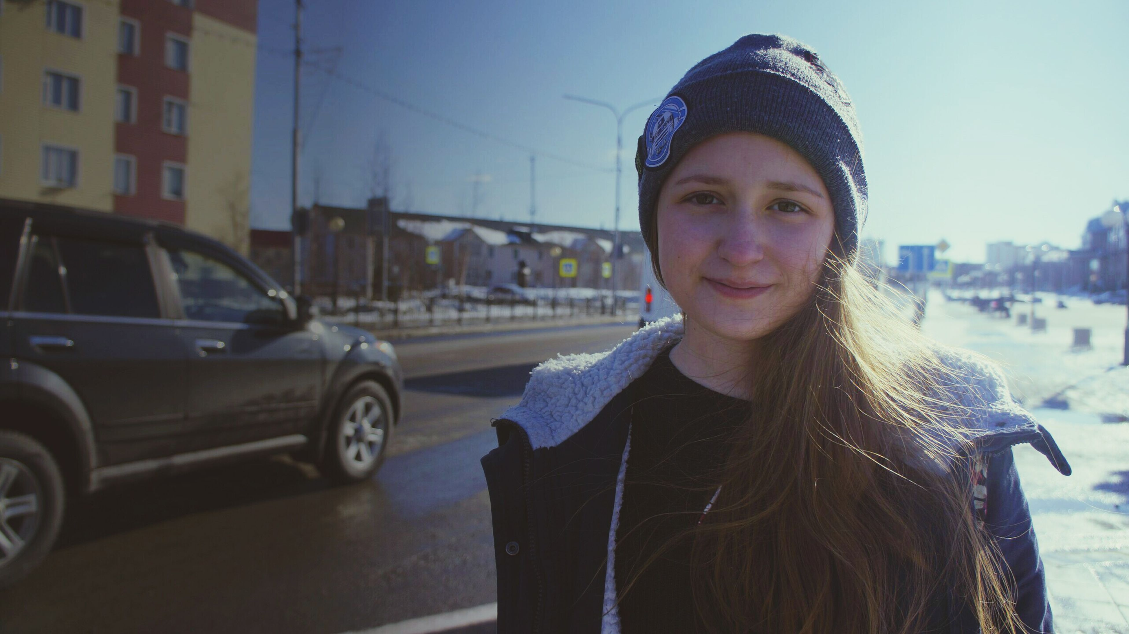 looking at camera, portrait, real people, one person, car, smiling, front view, lifestyles, transportation, building exterior, happiness, knit hat, architecture, built structure, day, leisure activity, warm clothing, outdoors, young adult, sky, people