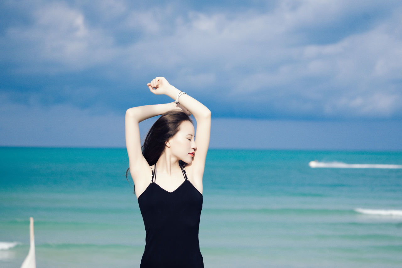 sea, sky, horizon over water, water, one person, young adult, real people, standing, nature, arms raised, beauty in nature, cloud - sky, outdoors, young women, day, scenics, leisure activity, tranquility, lifestyles, beautiful woman, beach, adult, people