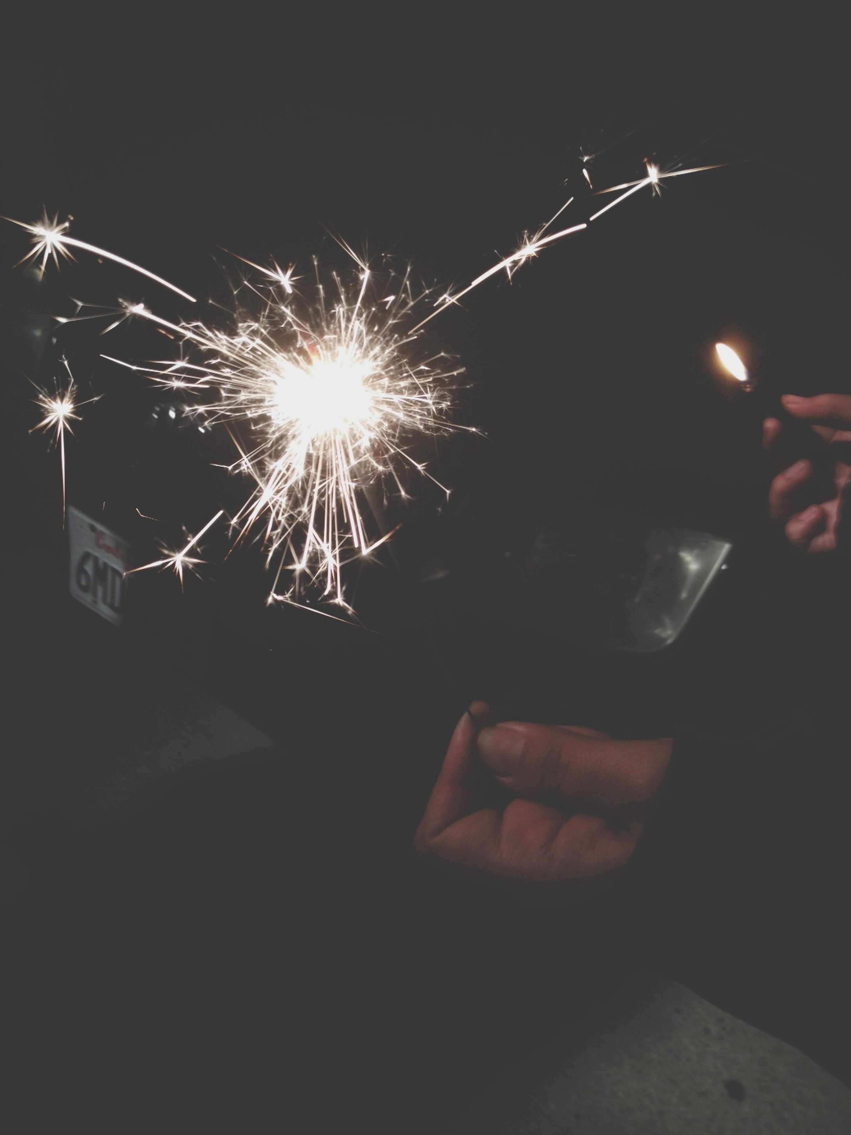 night, illuminated, arts culture and entertainment, fire - natural phenomenon, glowing, person, leisure activity, lifestyles, motion, burning, part of, sparks, celebration, men, holding, unrecognizable person, firework - man made object, flame