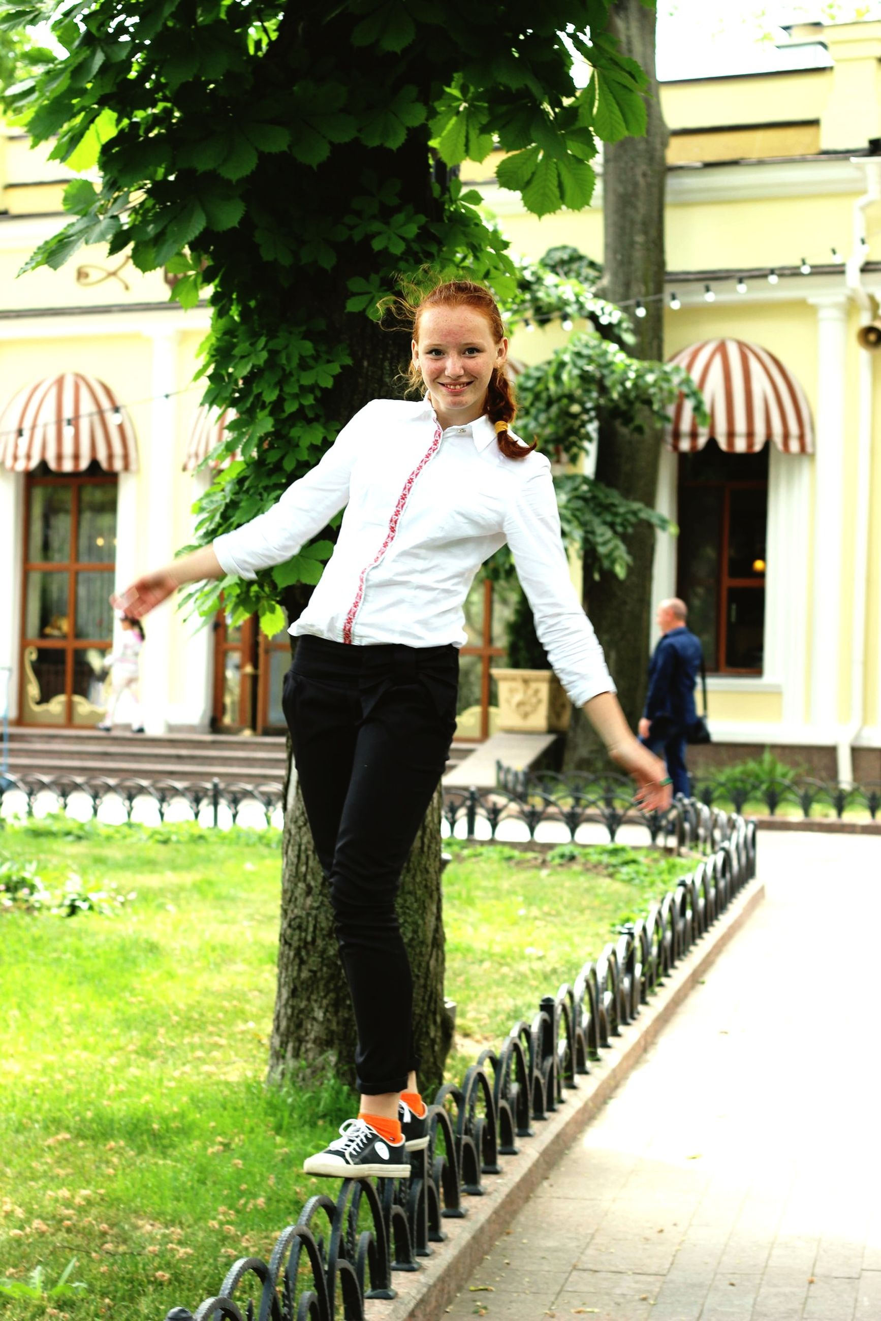 lifestyles, casual clothing, full length, building exterior, leisure activity, built structure, architecture, young adult, grass, standing, person, front view, young women, tree, green color, looking at camera, day