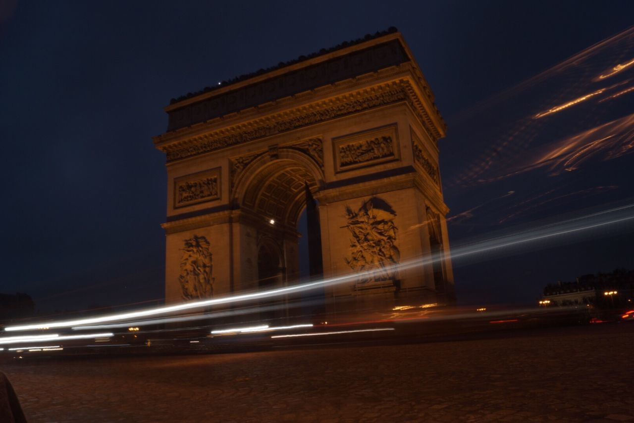 blurred motion, night, speed, motion, illuminated, long exposure, architecture, light trail, triumphal arch, transportation, history, travel destinations, sky, outdoors, monument, low angle view, built structure, city, no people