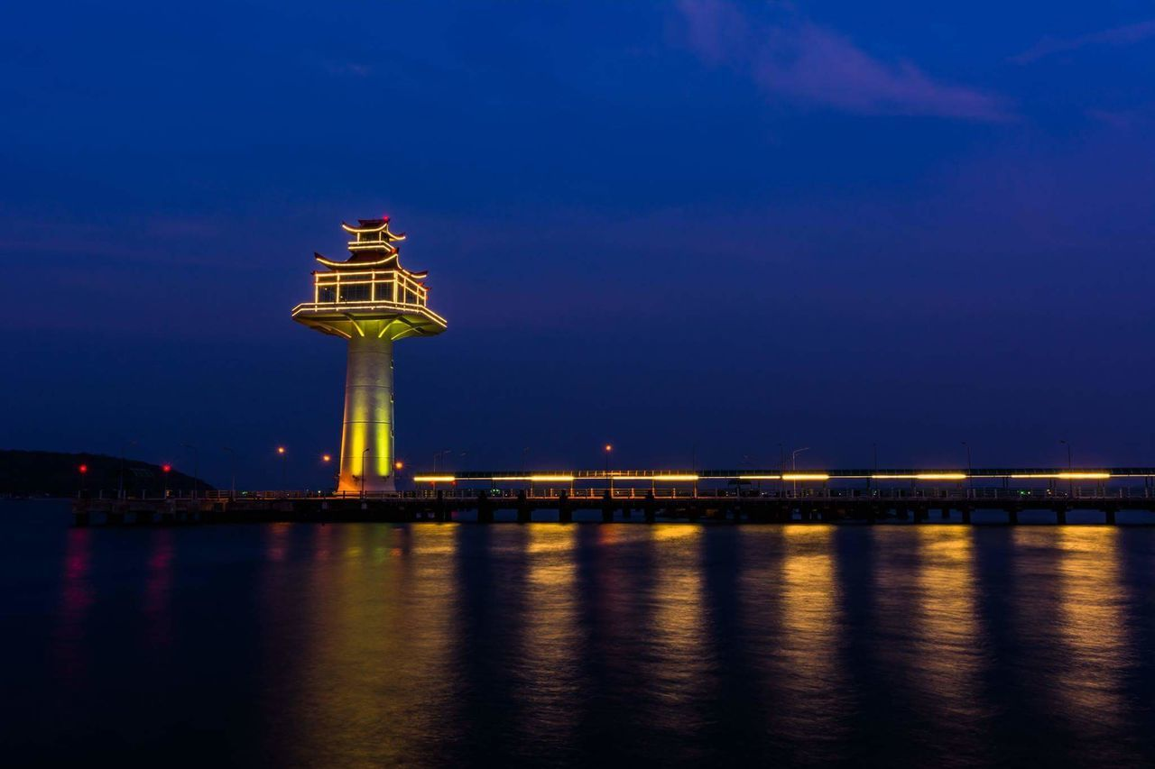 night, illuminated, architecture, built structure, sky, reflection, travel destinations, outdoors, blue, no people, water, sunset, lighthouse, sea, building exterior, nature